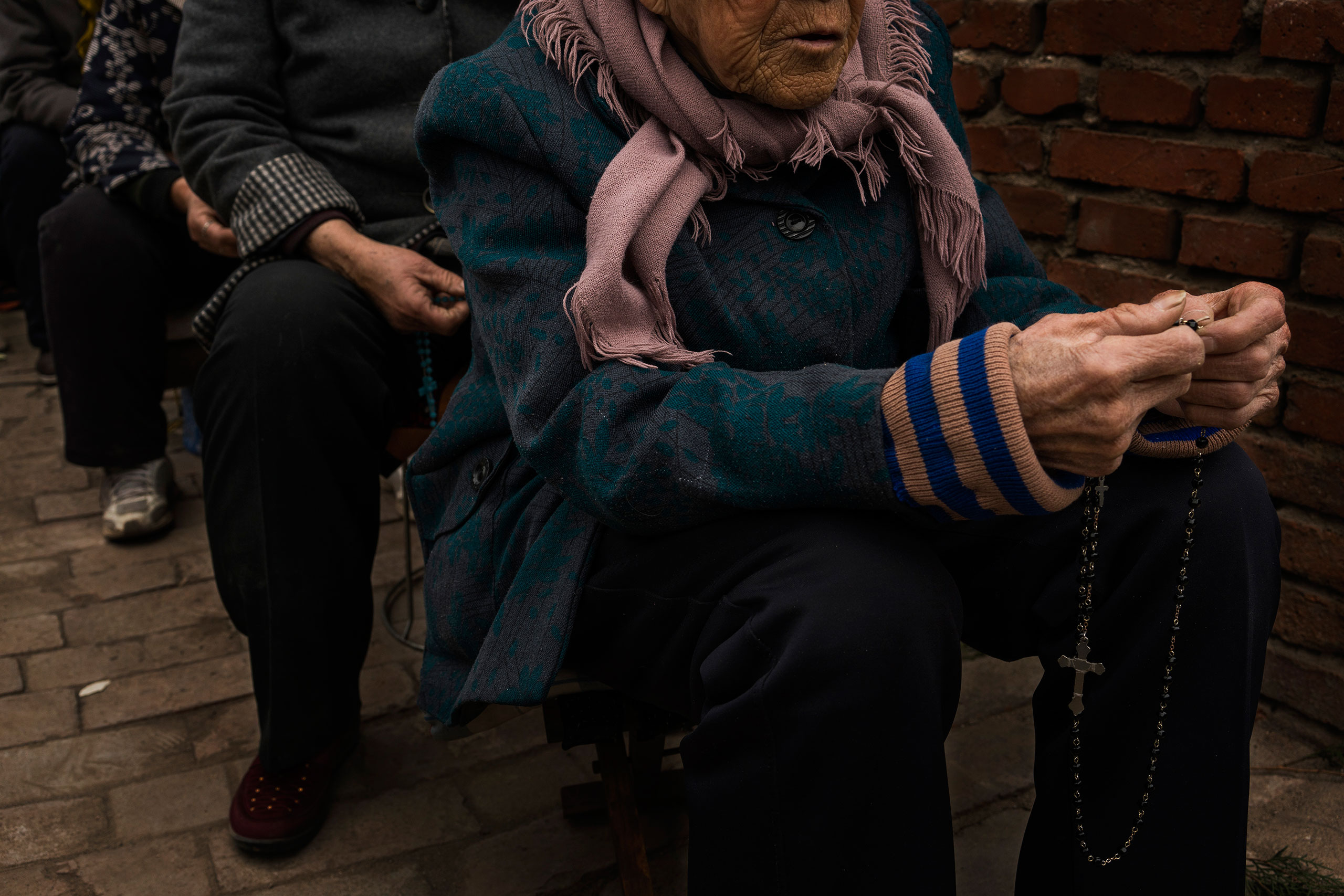A parishioner thumbs her Rosemary beads during an underground Palm Sunday service in the yard of a house in Youtong village, Shijiazhuang, China, March 20, 2016.