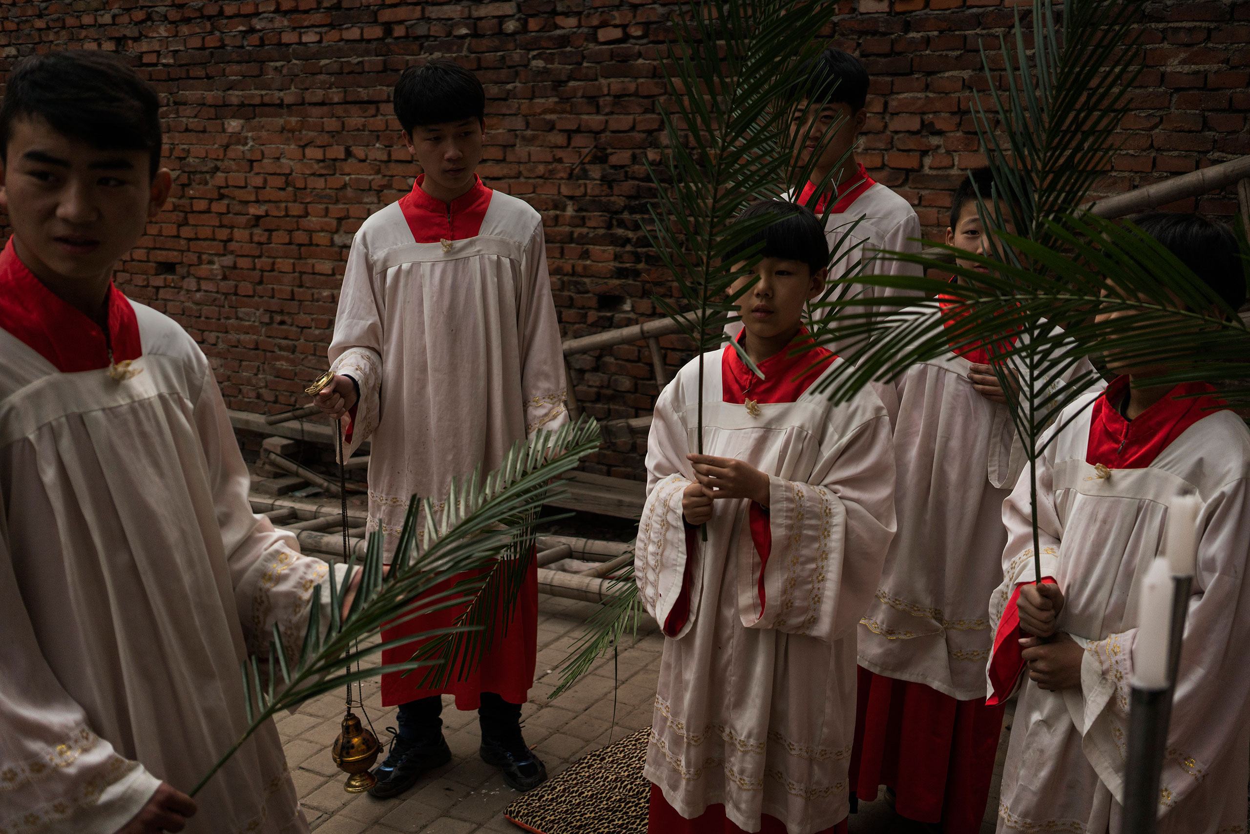 Altar boys prepare for an underground Palm Sunday service in the yard of a house in Youtong village, Shijiazhuang, China, March 20, 2016.
