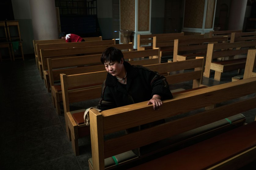 A volunteer cleans a pew ahead of a Mass at the government sanctioned Catholic Church of Virgin Mary in Donglu, near Baoding, China, March 20, 2016. Hebei has one of the largest populations of Christians in China who practice at both legal and underground Churches.