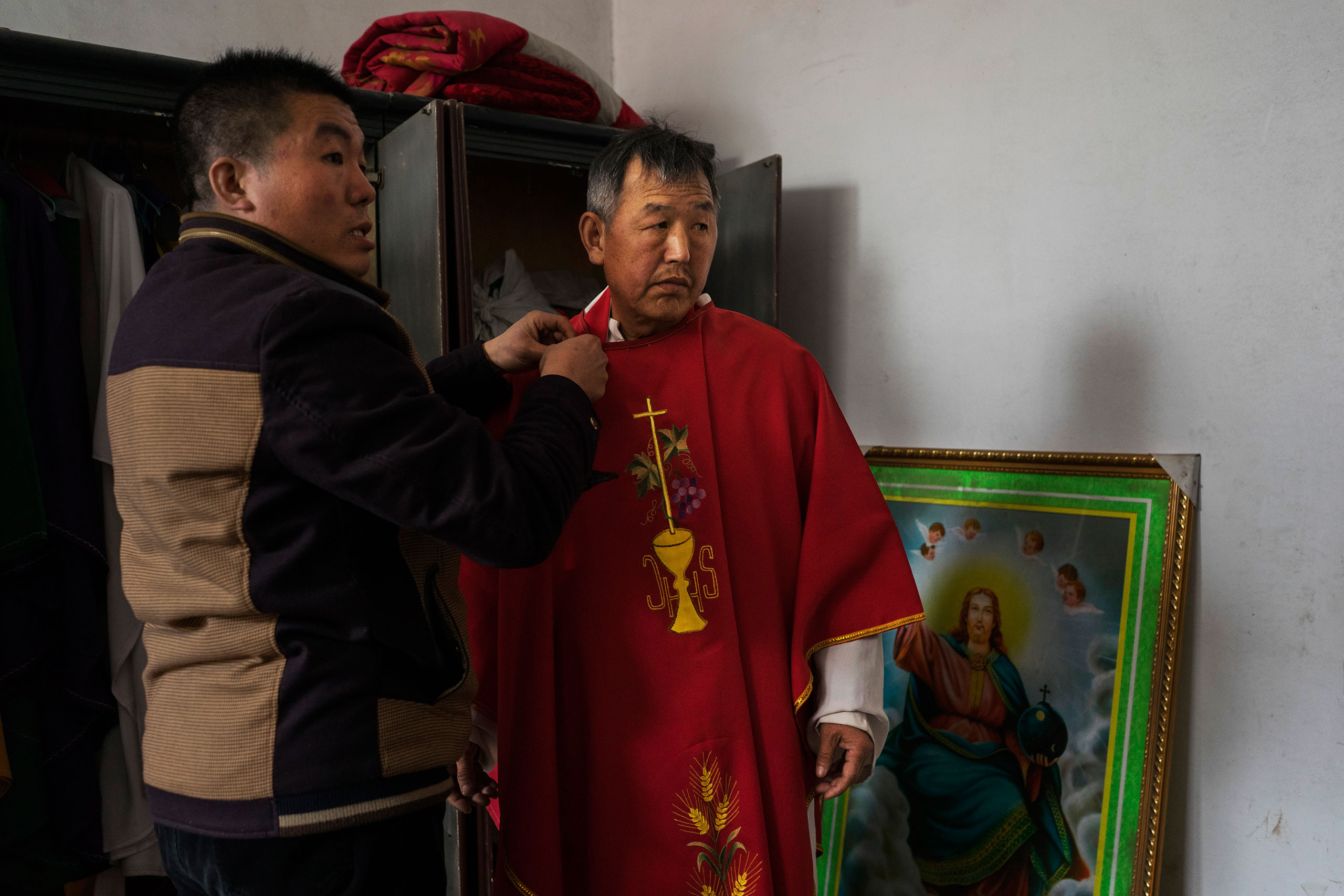 Dong Baolu, a dissident Catholic priest, is helped to dress ahead of a Palm Sunday service at an underground church service in the yard of a house in Youtong village, Shijiazhuang, China, March 20, 2016.