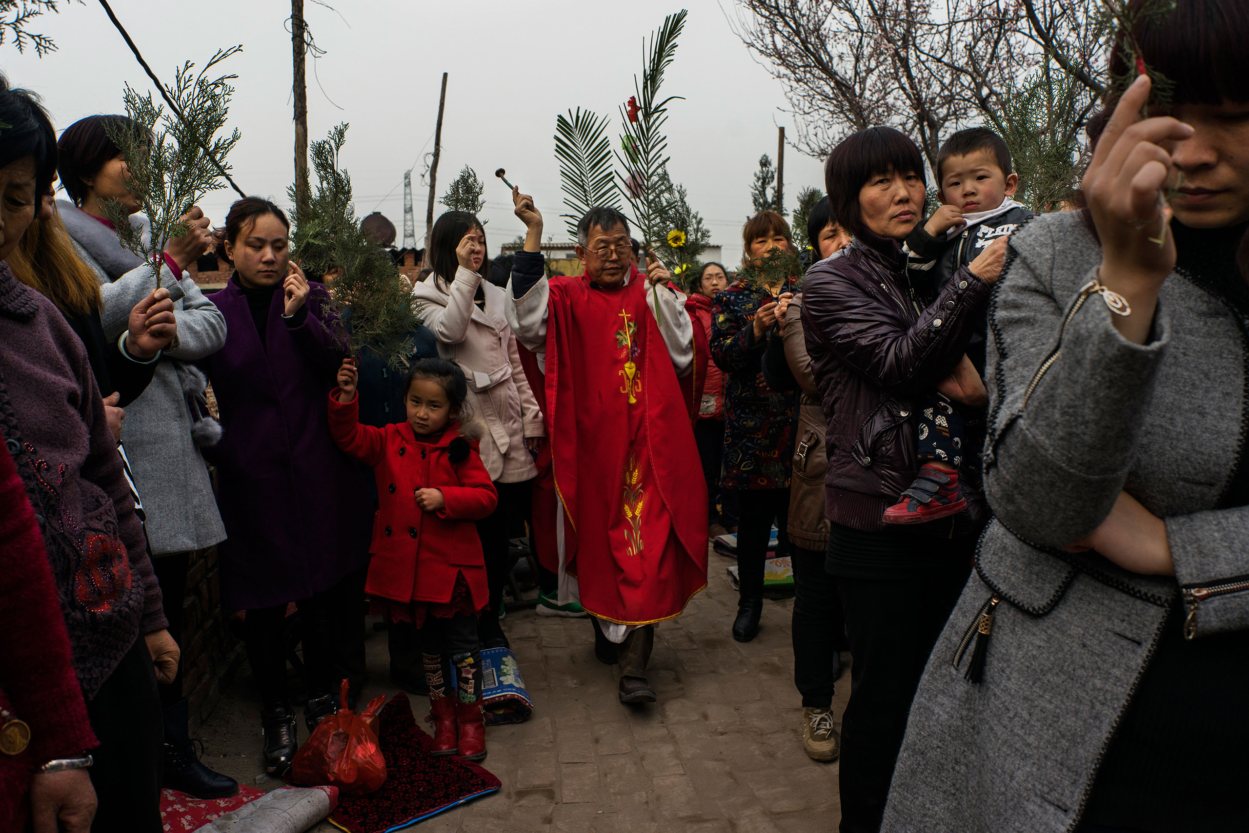 Dissident Catholic Priest Dong Baolu leads a procession through the congregation at an underground Palm Sunday service in the yard of a house in Youtong village, Shijiazhuang, China, March 20, 2016.