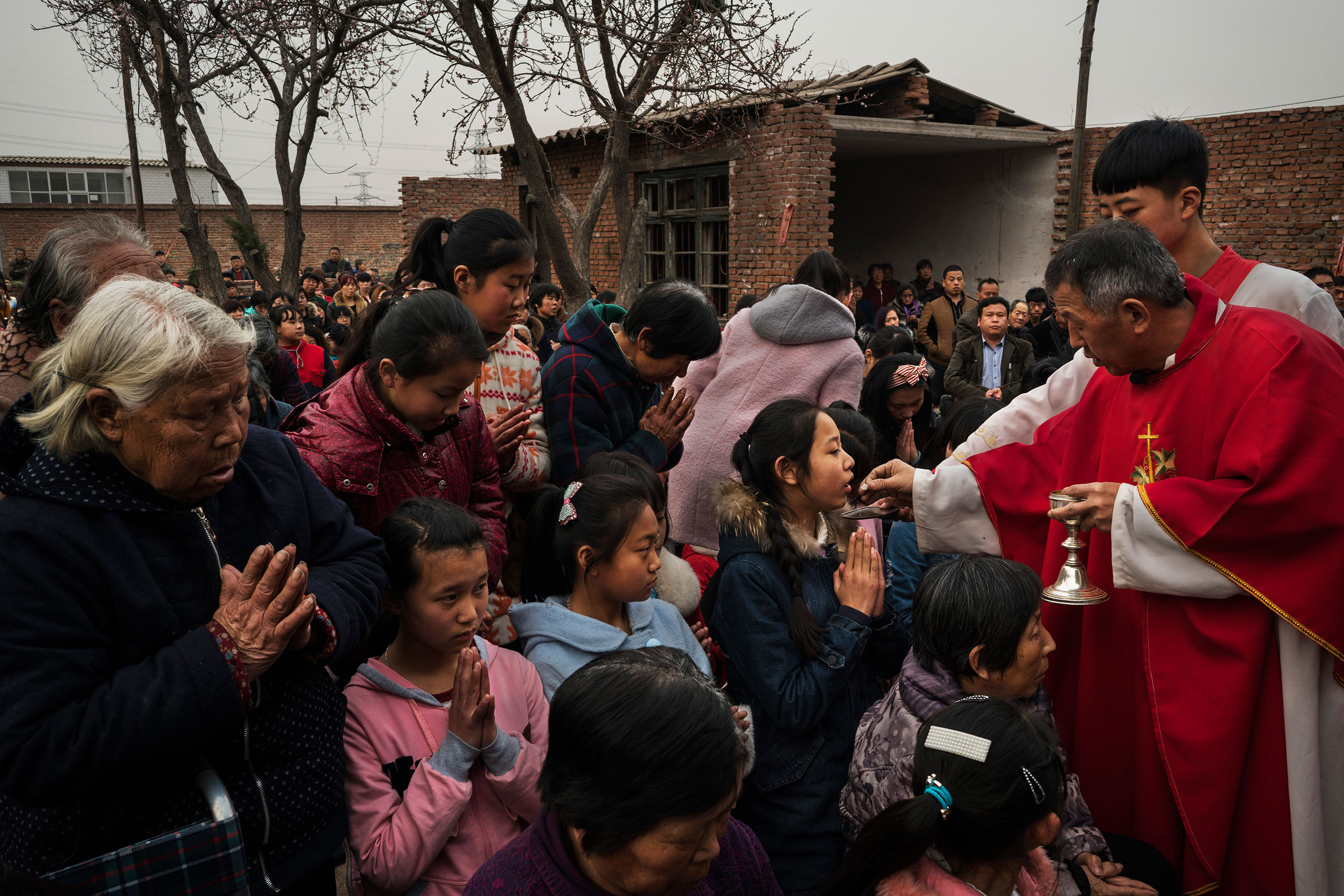 Villagers receive Communion from dissident Catholic Priest Dong Baolu at an underground Palm Sunday service in the yard of a house in Youtong village, Shijiazhuang, China, March 20, 2016.
