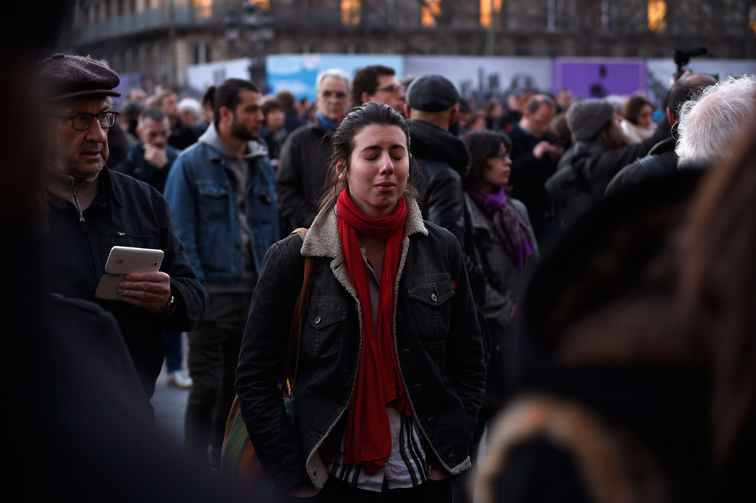A woman mourning the victims of the Brussels terrorist attacks cries in front of the the city hall of Paris where people gather as a tribute, March 22, 2016.