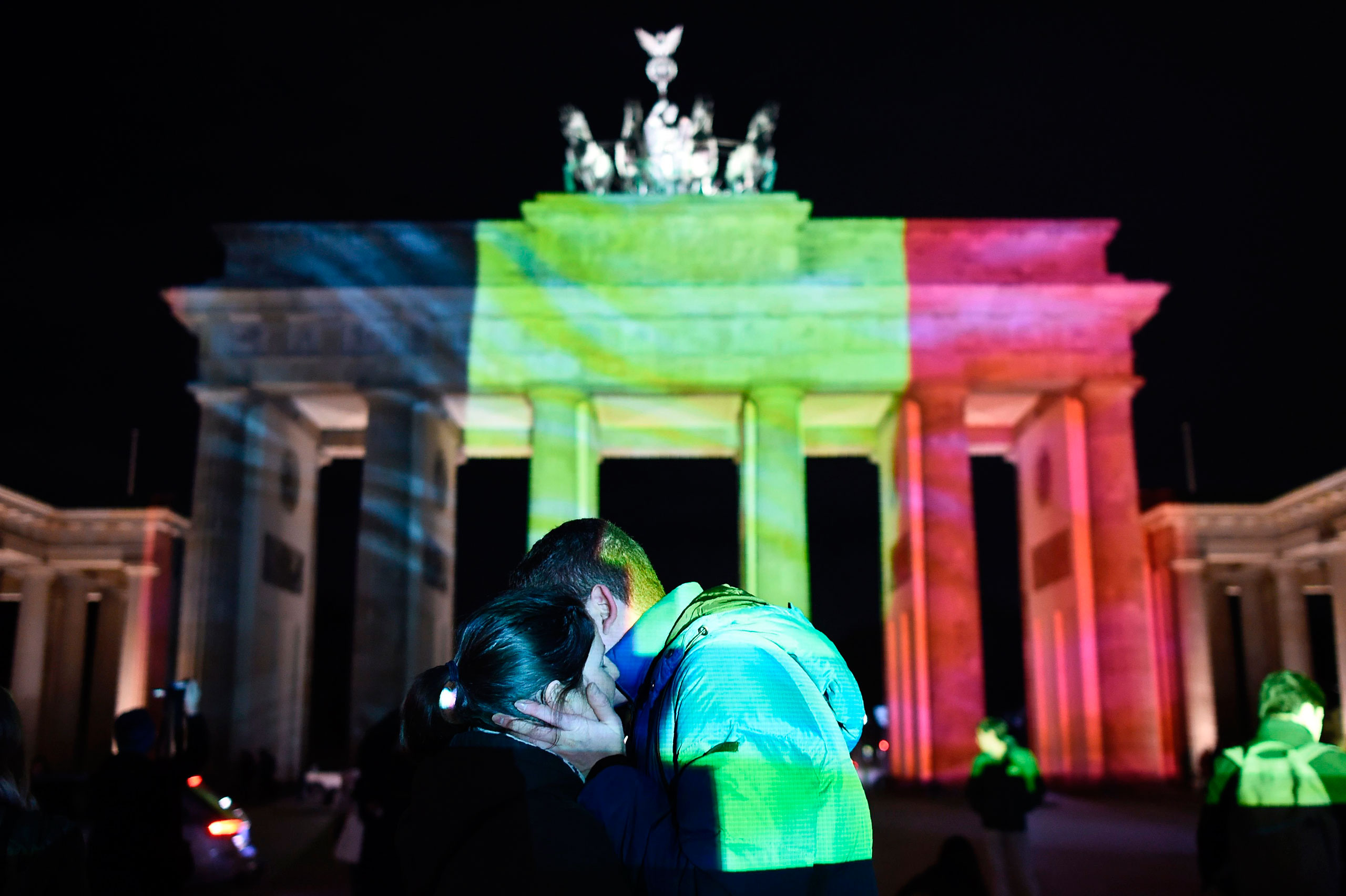 A couple embraces as the colors of the Belgian flag are projected on to the Brandenburg Gate in Berlin, March 22, 2016.