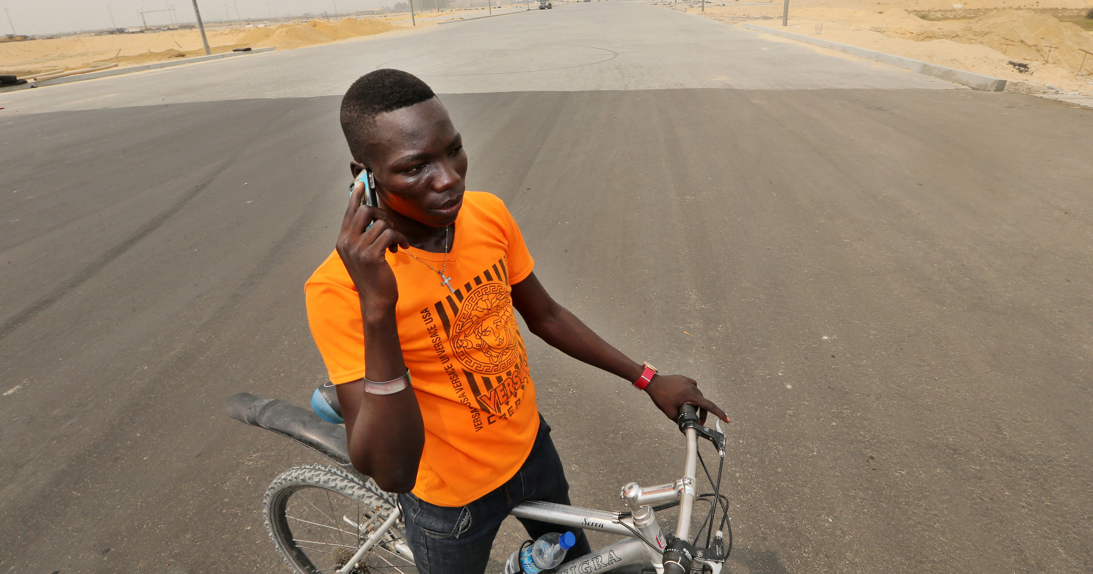 A cyclist stops to make a mobile phone call on a newly surfaced boulevard at the Eko Atlantic City site, developed by Eko Atlantic, near Victoria Island in Lagos, Nigeria on Feb. 12, 2016.