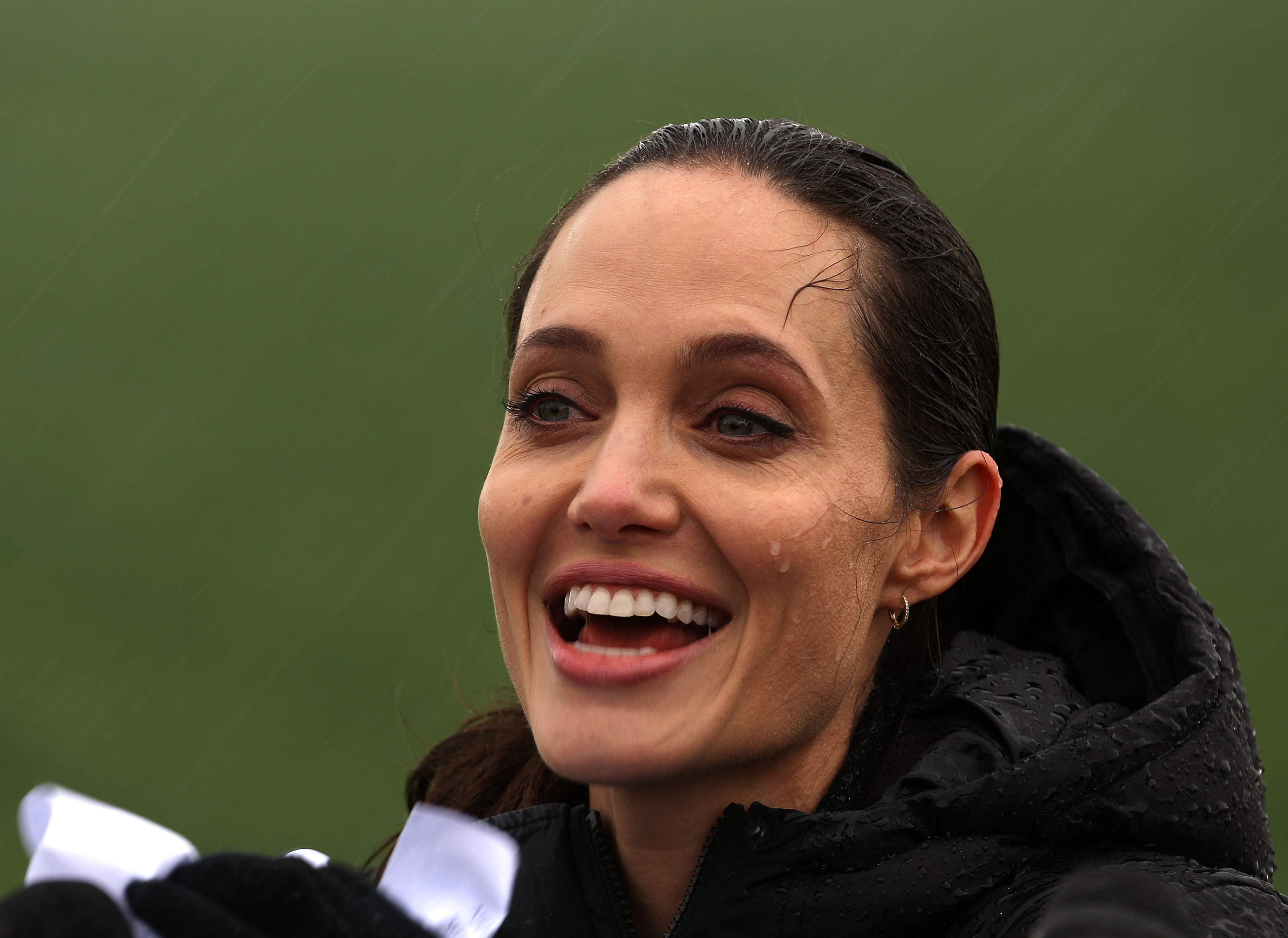 Special envoy of the UN High Commissioner for Refugees, US actress Angelina Jolie reacts during a press conference under the rain as part of her visit at a Syrian refugee camp near the city of Zahle in Lebanon's Bekaa Valley on March 15, 2016.