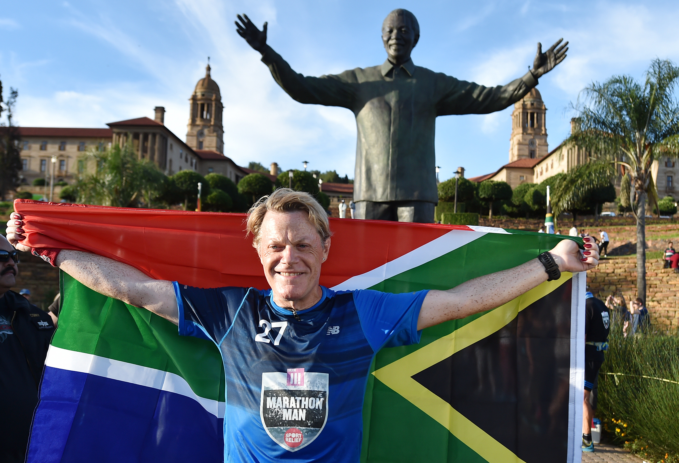 British comedian Eddie Izzard holds a South African flag beneath a statue of former president Nelson Mandela in Pretoria, South Africa, March 20, 2016