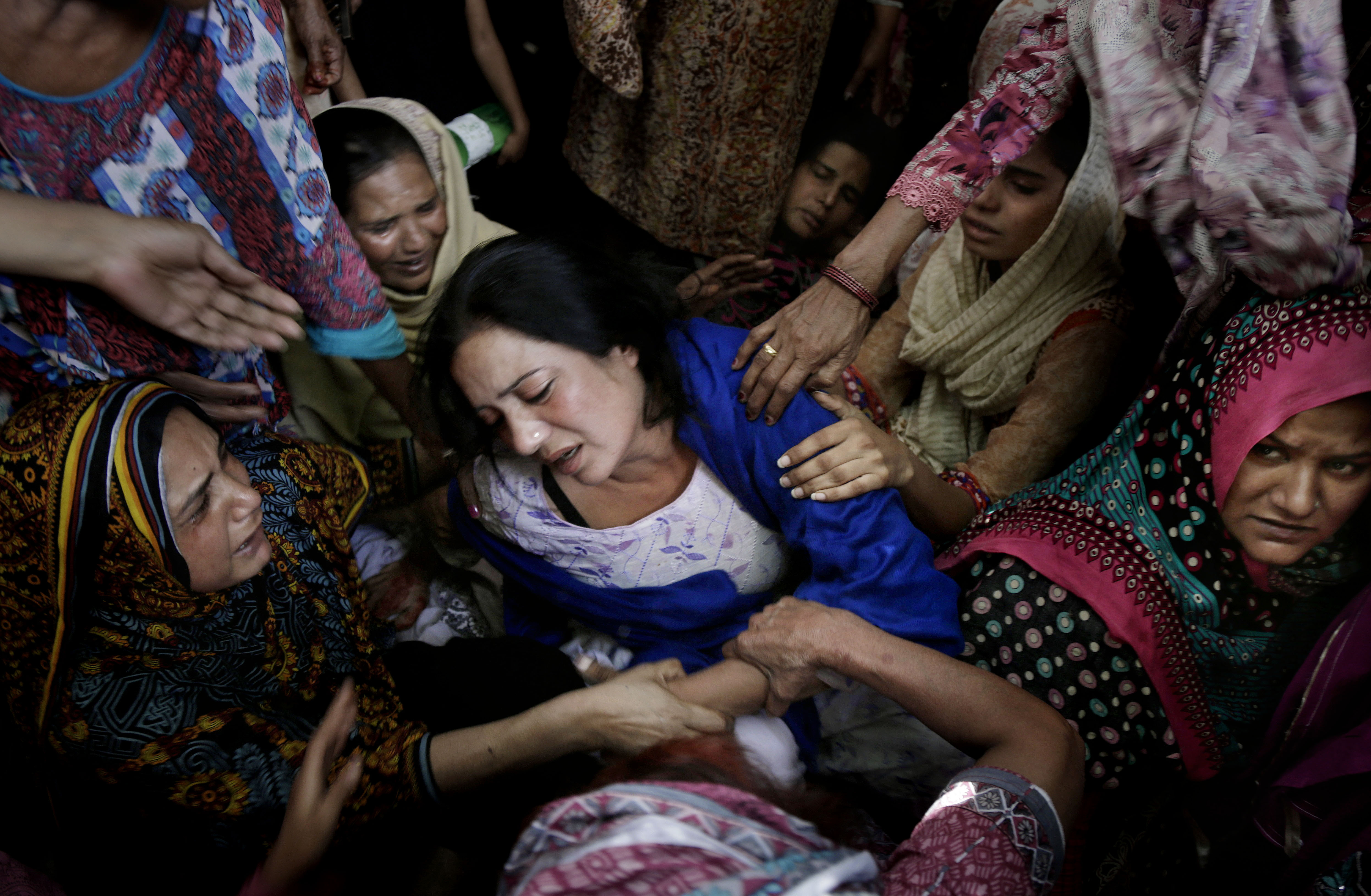 Women try to comfort a mother who lost her son in bomb attack in Lahore, Pakistan, March 28, 2016.