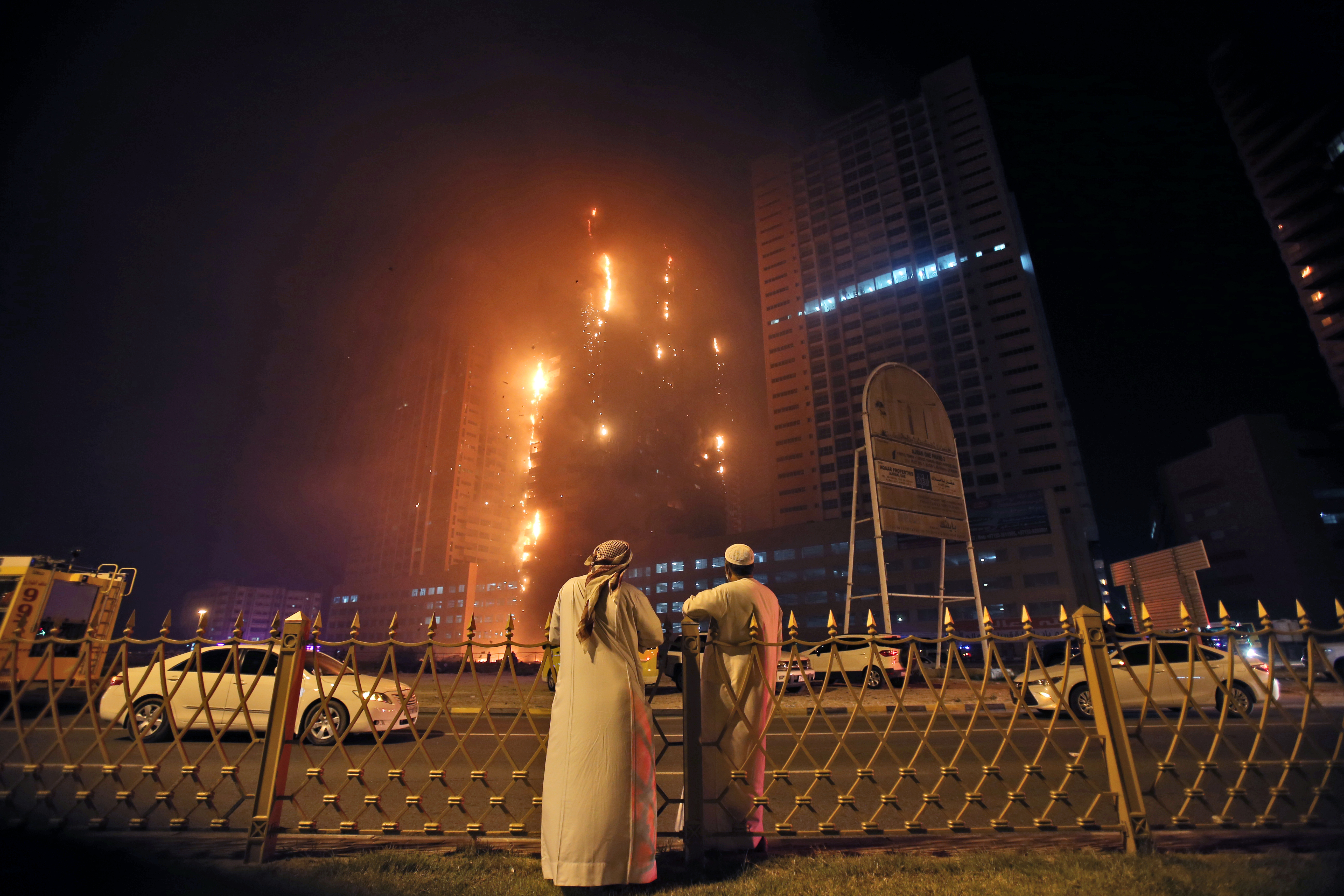 Two Emirati officials watch a high-rise building as a fire spreads up the side of the building in Ajman, United Arab Emirates, early, March 29, 2016.