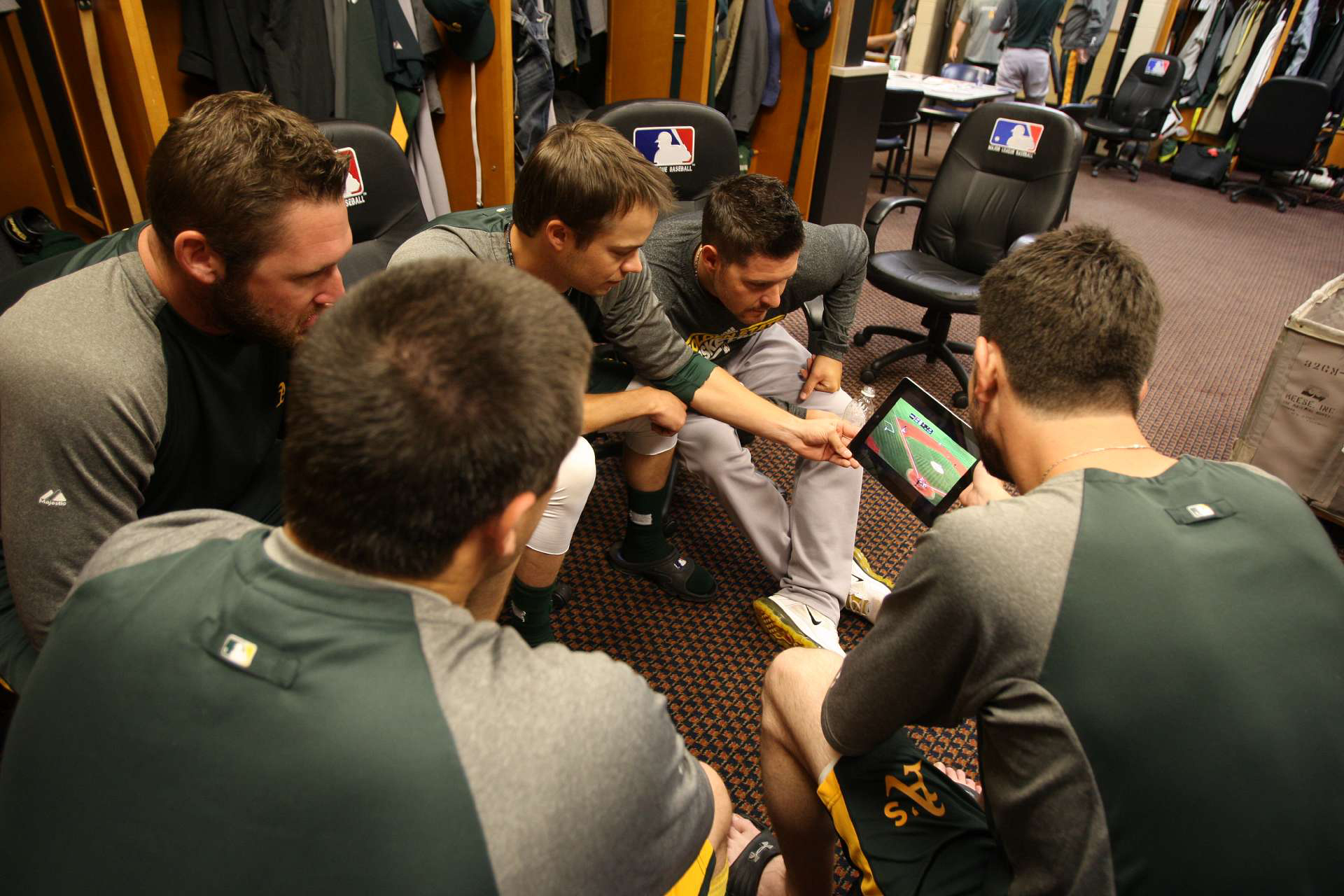 Members of the Oakland Athletics pitching staff watch highlights of the Athletics on an iPad in the clubhouse prior to the game against the Detroit Tigers at Comerica Park on October 6, 2012 in Detroit, Michigan.