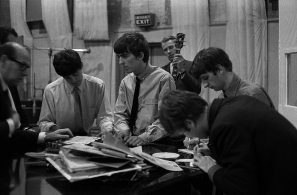 The Beatles sign documents for music publisher Dick James in Studio 2 at Abbey Road in London recording the single 'She Loves You', 1st July 1963, L-R Dick James, Paul McCartney, George Harrison, producer George Martin (in background), John Lennon (writing) and Ringo Starr.