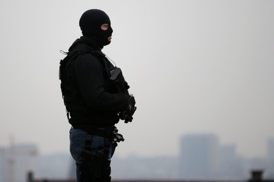 A member of the special police forces stands guard outside the Council Chamber of Brussels during investigations into the Paris and Brussels terror attacks on March 24, 2016.