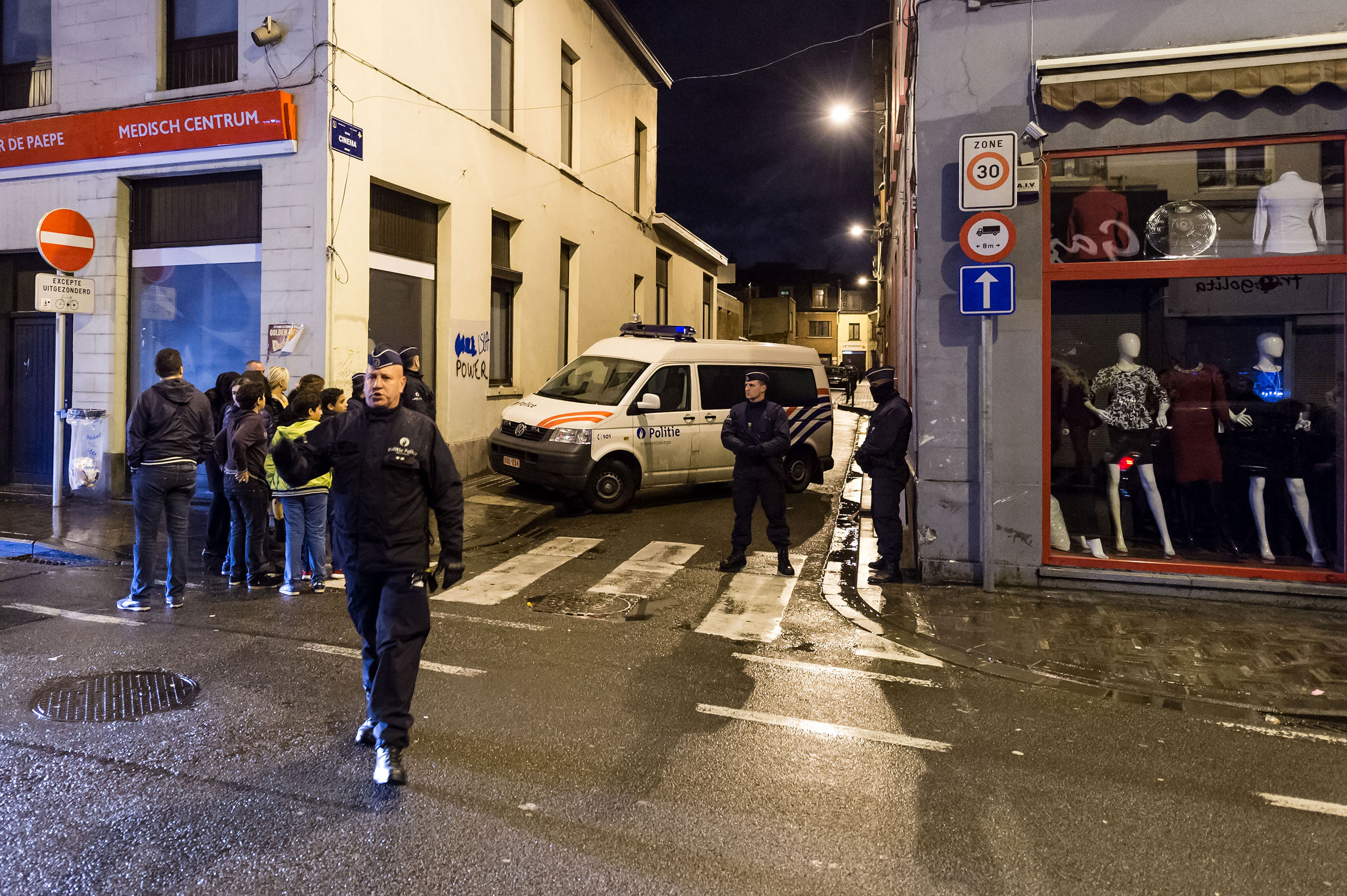 Police guard a street while special intervention forces search a house in the Molenbeek neighborhood of Brussels, Belgium, Nov. 17, 2015.