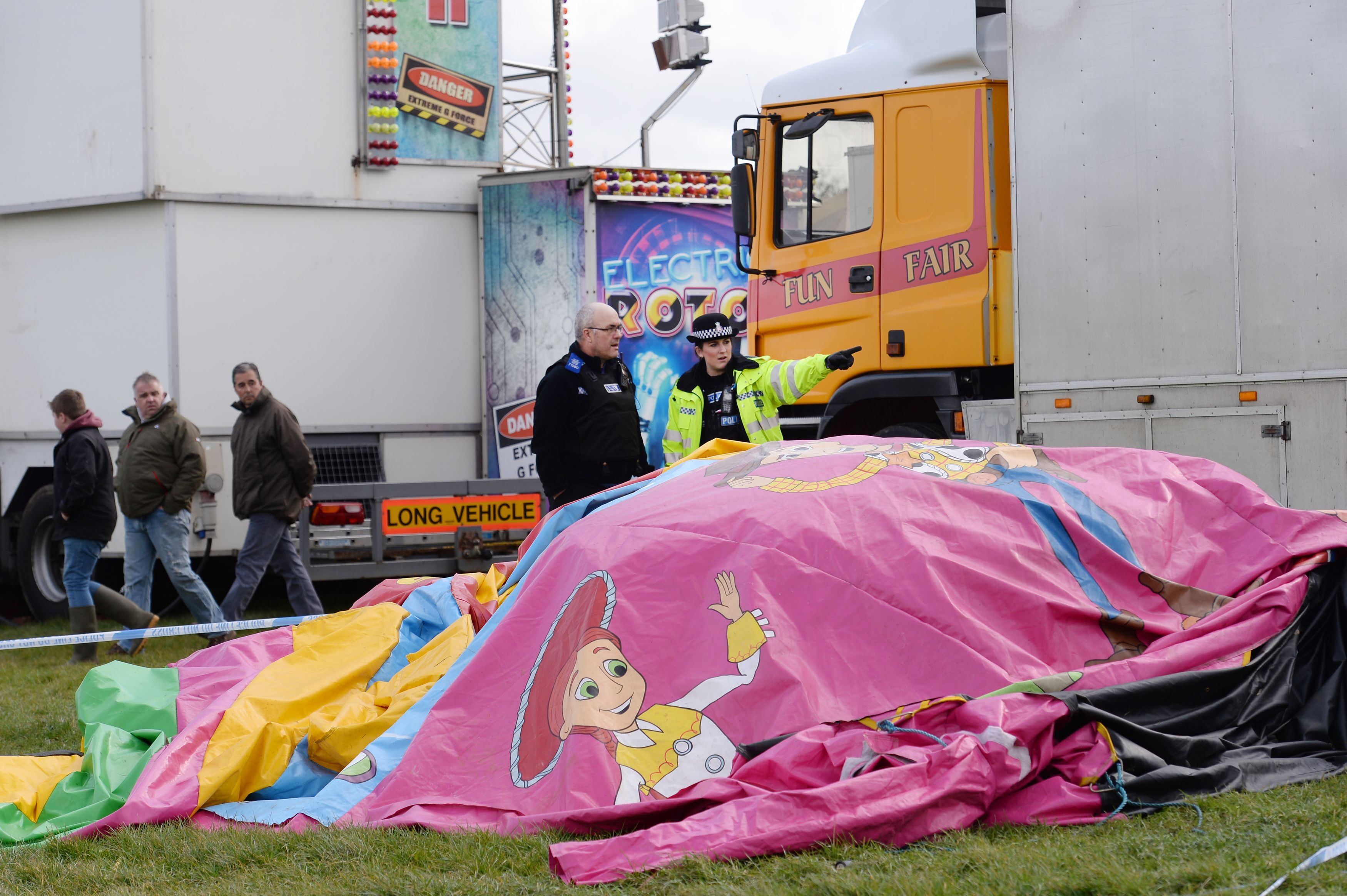 Police and forensic officers attend the scene where a seven-year old girl died after she was blown by the wind about 150 metres on a bouncy castle on March 27, 2016.