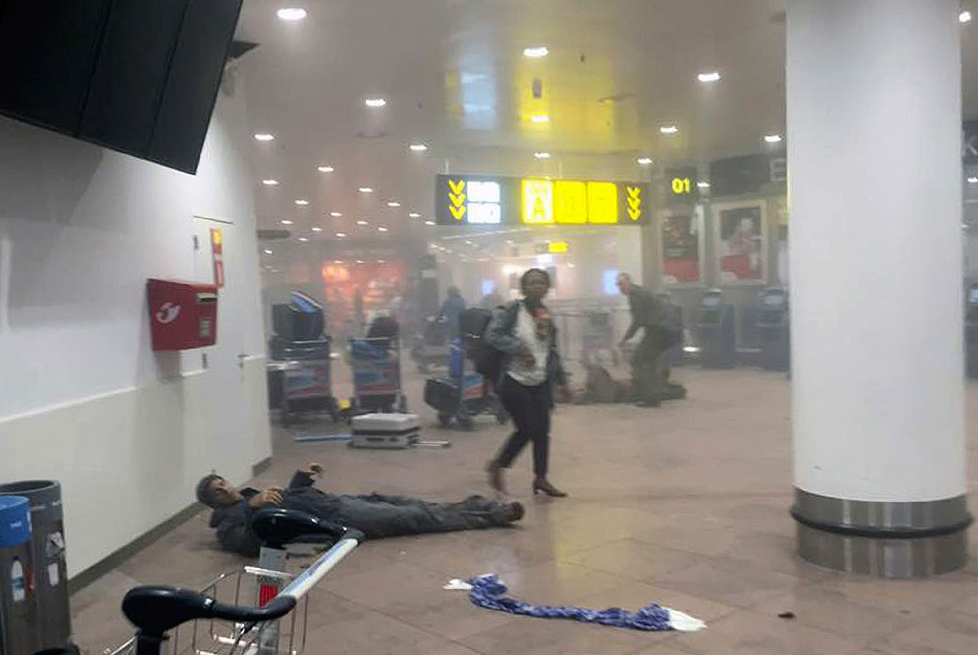 A wounded man lays on the ground after a bomb blast at the airport in Brussels on March 22, 2016