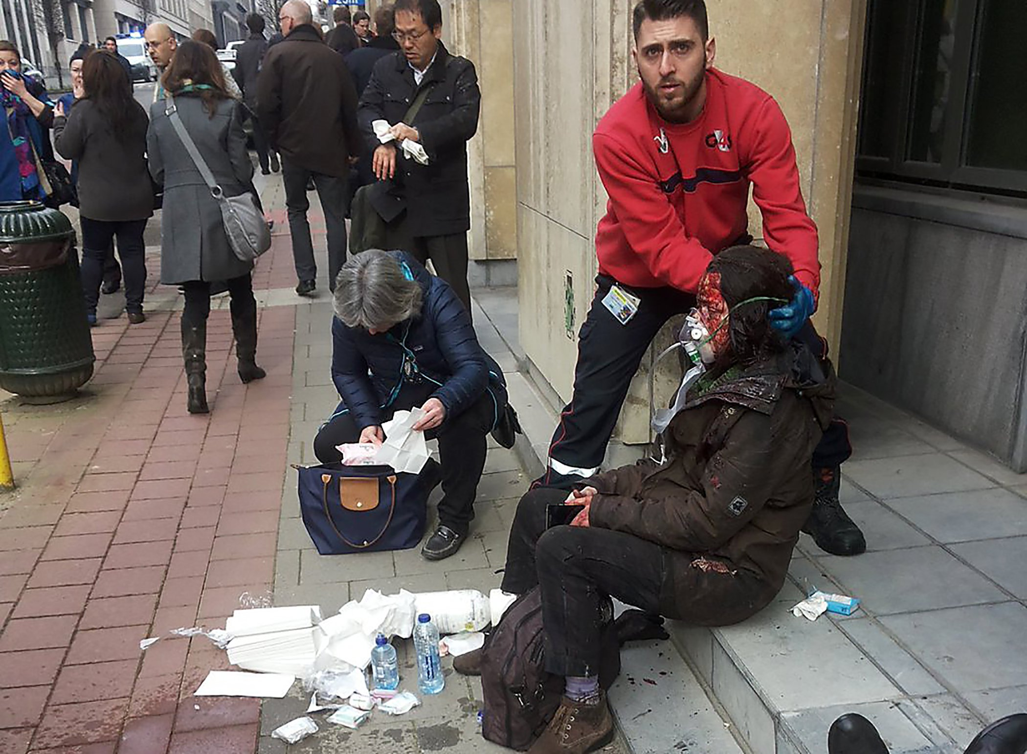 A private security guard helps a wounded women outside the Maalbeek metro station after a blast at this station located near the EU institutions, in Brussels on March 21, 2016.