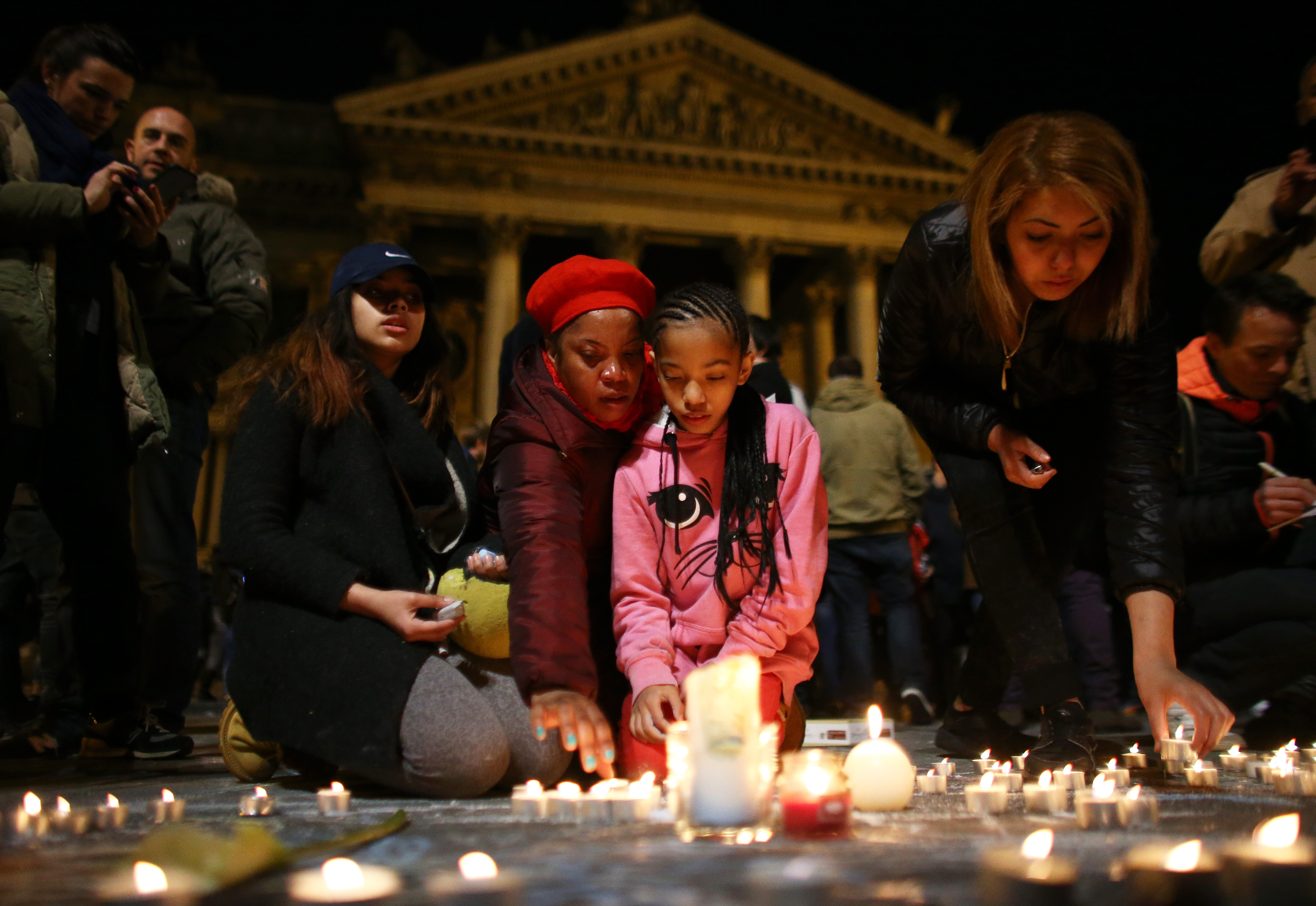 A young girl lights a candle at the Place de la Bourse following the attacks on March 22, 2016 in Brussels, Belgium.