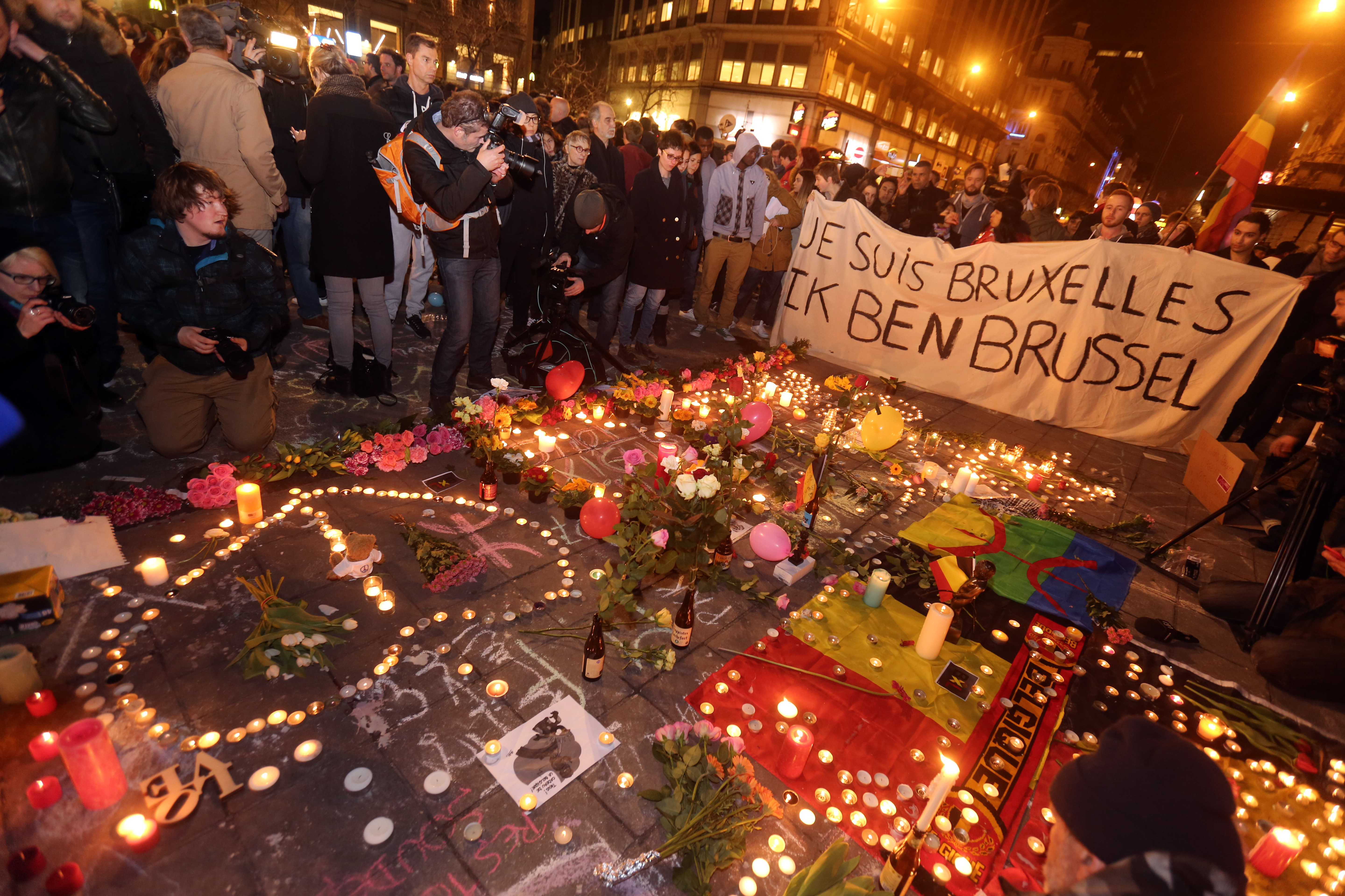 People gather to leave tributes at the Place de la Bourse following the terrorist attacks on March 22, 2016 in Brussels, Belgium.
