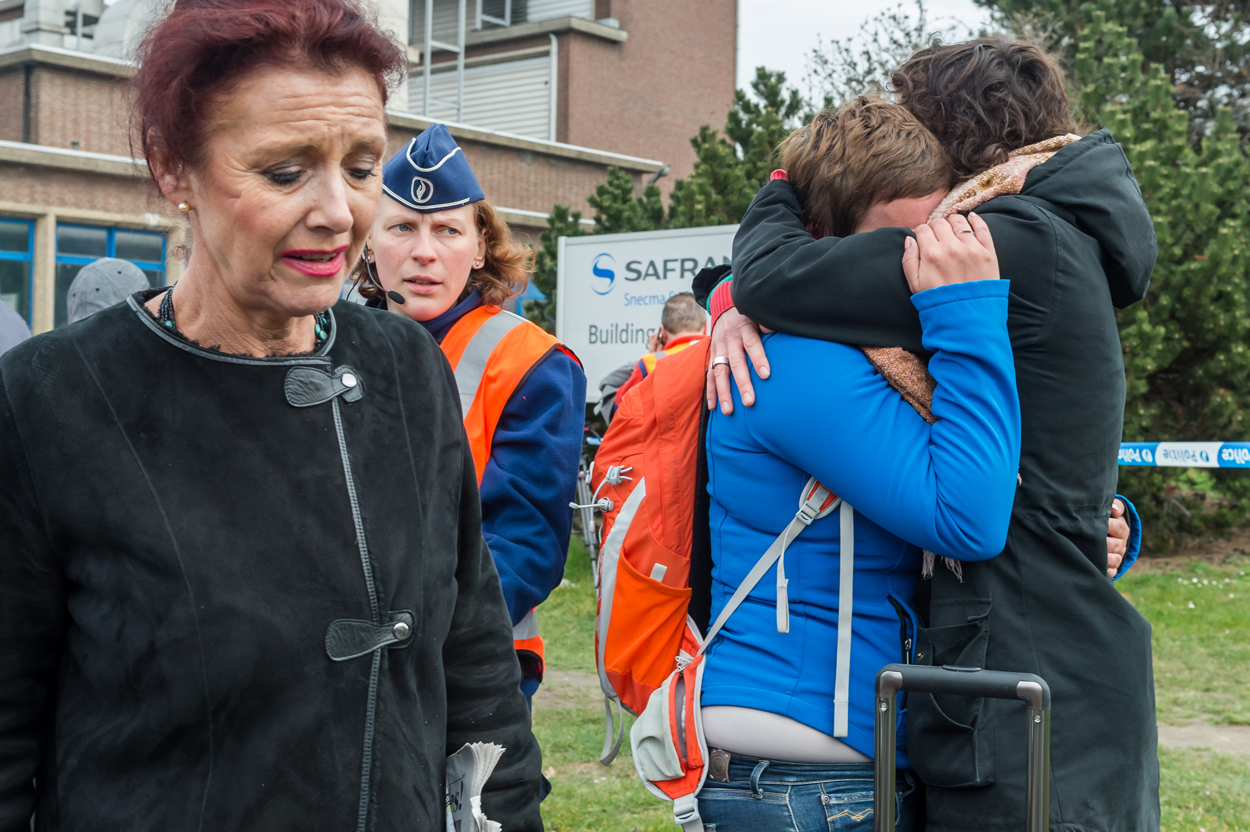 People react outside Brussels airport after explosions rocked the facility in Brussels, Belgium on March 22, 2016.