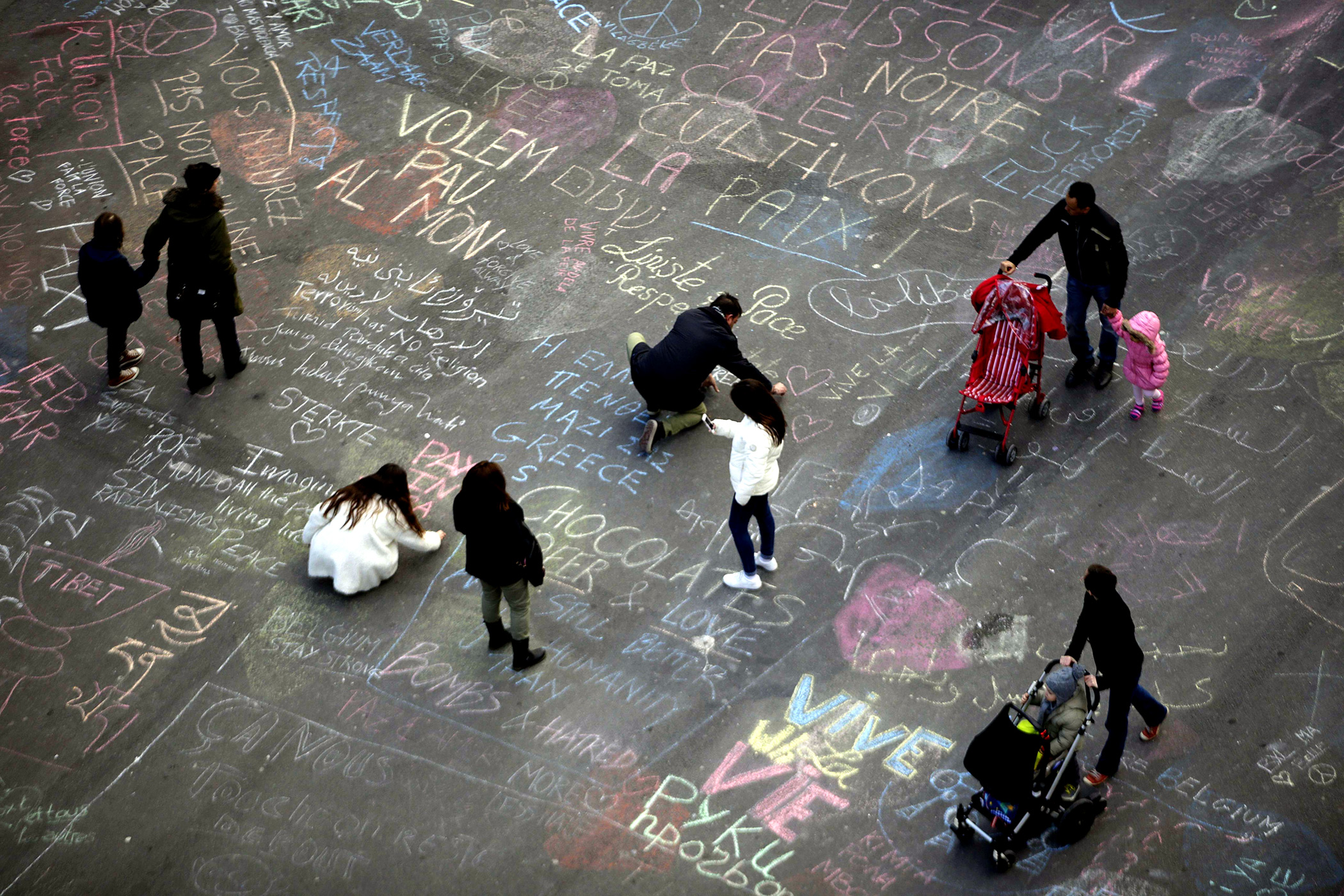 People write messages in chalk at Place de la Bourse following attacks in Brussels, Belgium, March 22, 2016.