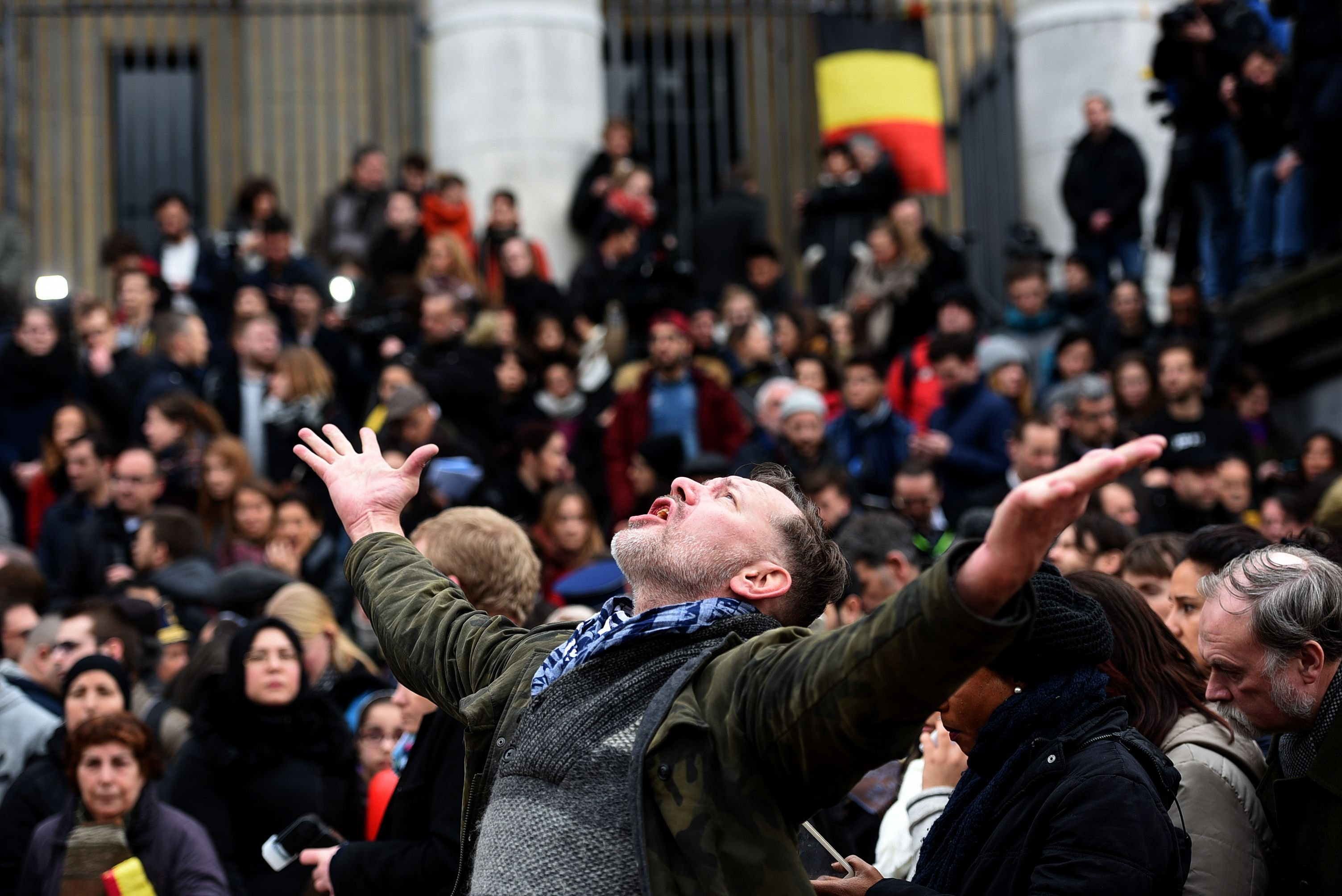 A man reacts as people gather to observe a minute of silence in memory of the victims of the Brussels airport and metro bombings, on March 23, 2016.