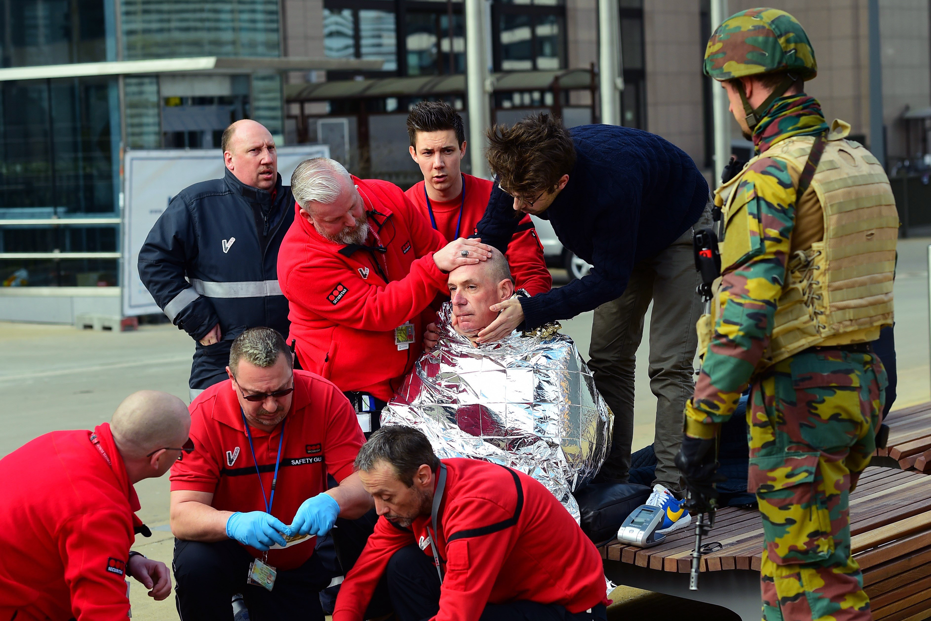 A victim receives first aid by rescuers, on March 22, 2016, near Maelbeek metro station in Brussels, after a blast at this station near the E.U. institutions caused deaths and injuries