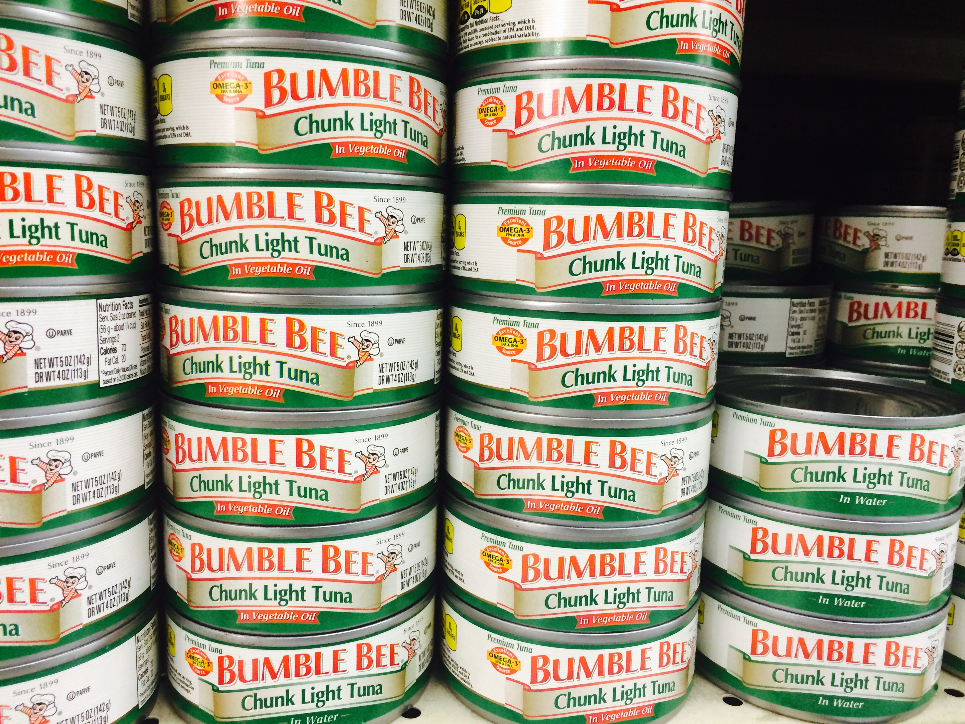 Bumble Bee chunk light tuna can is seen on a shelf at a grocery store.