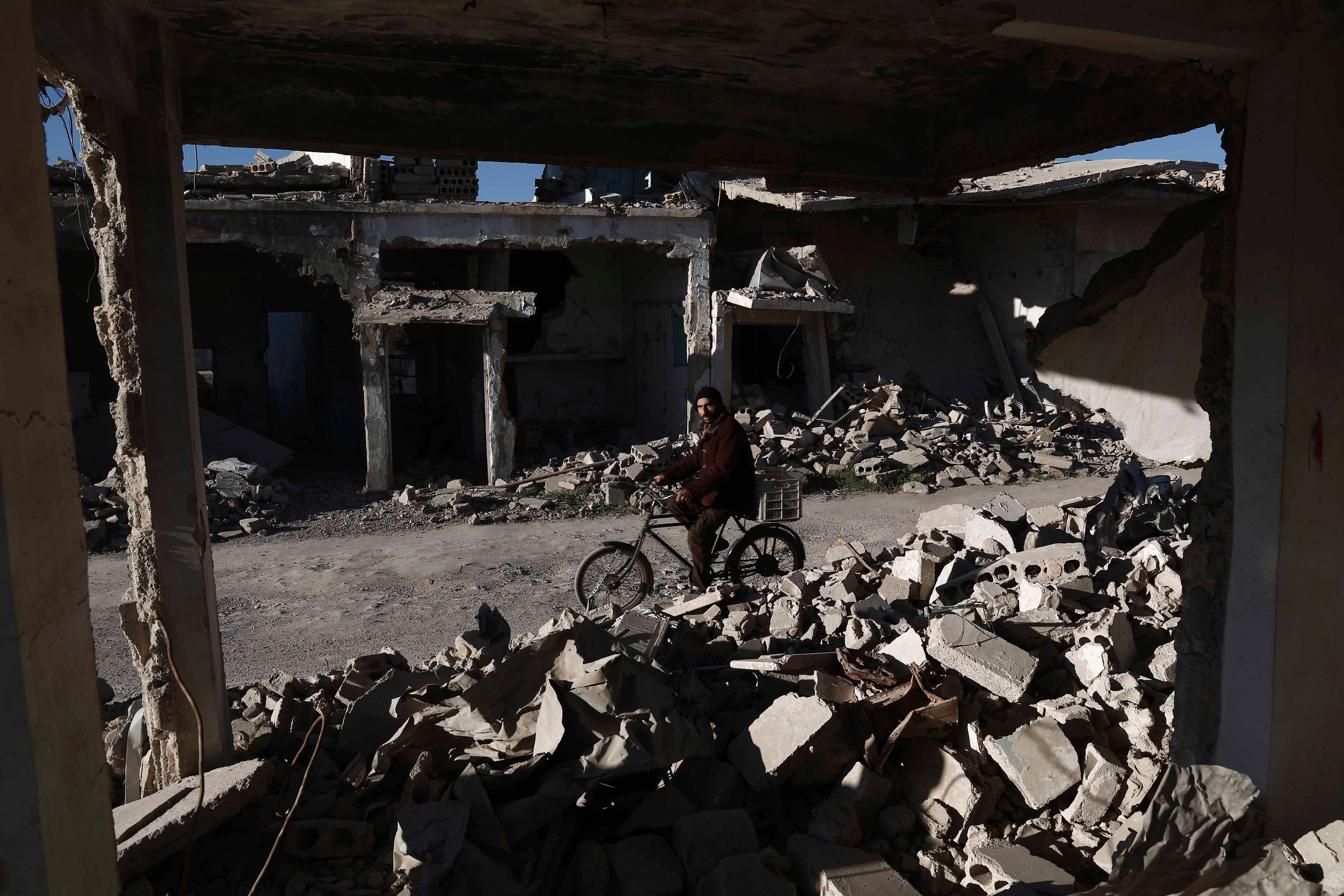 A Syrian man rides his bicycle past the rubble of destroyed buildings on March 7, 2016, in the rebel-held town of Douma, on the outskirts of Damascus.
