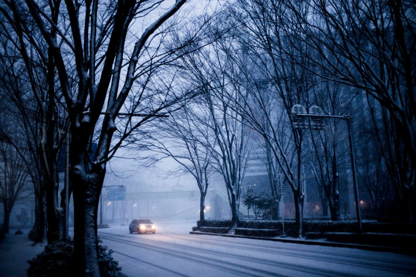 A car drives down the empty streets of Fukushima City during a snow storm on March 1, 2016. The city is located about 70km from the Fukushima Daiichi nuclear power plant.
