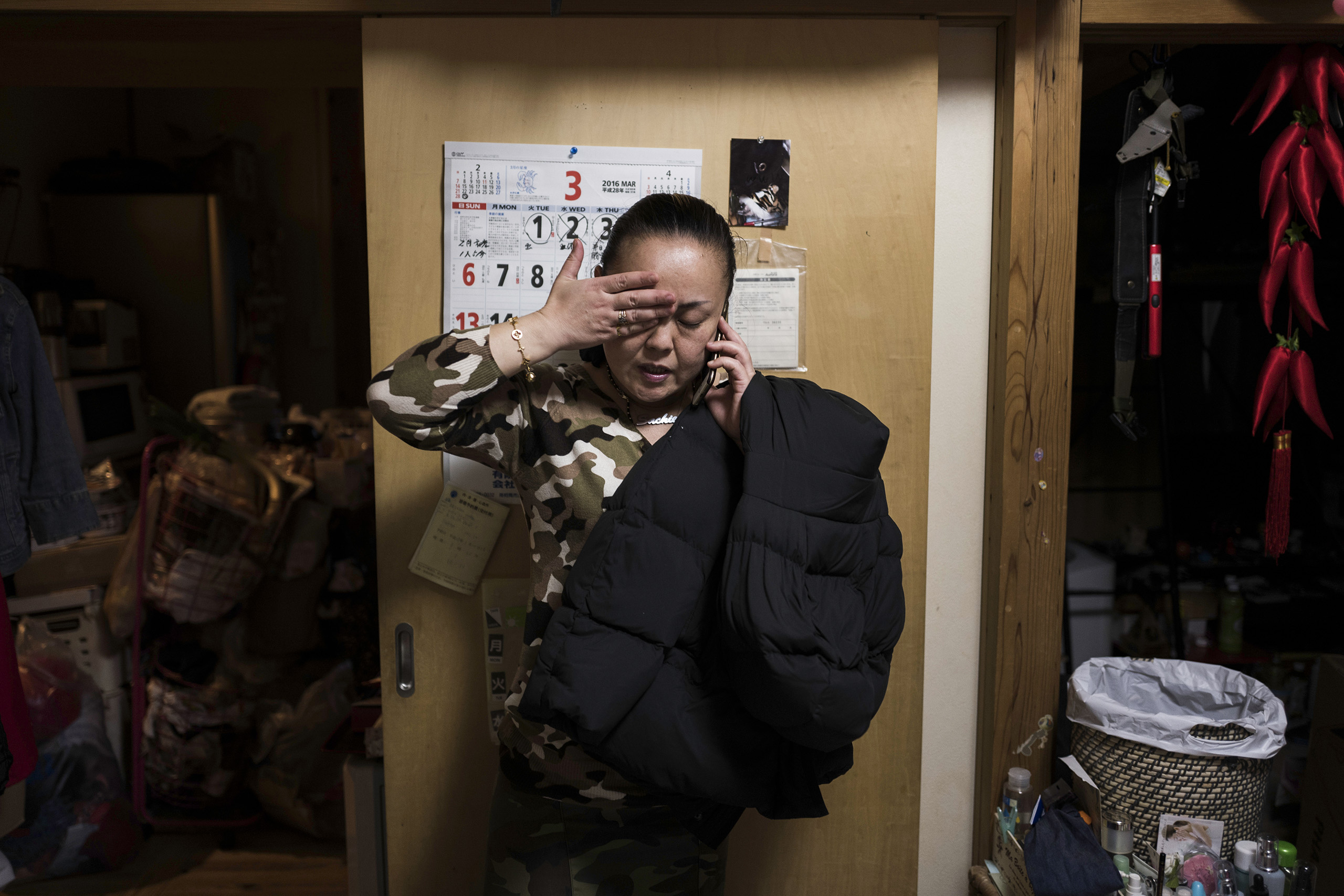 Sachie Matsumoto talks on the phone inside her temporary house in Minamisoma, Fukushima, March 3, 2016. Her son, a decontamination worker, tried to commit suicide. Her family will soon move to a new home built with savings and compensation money.