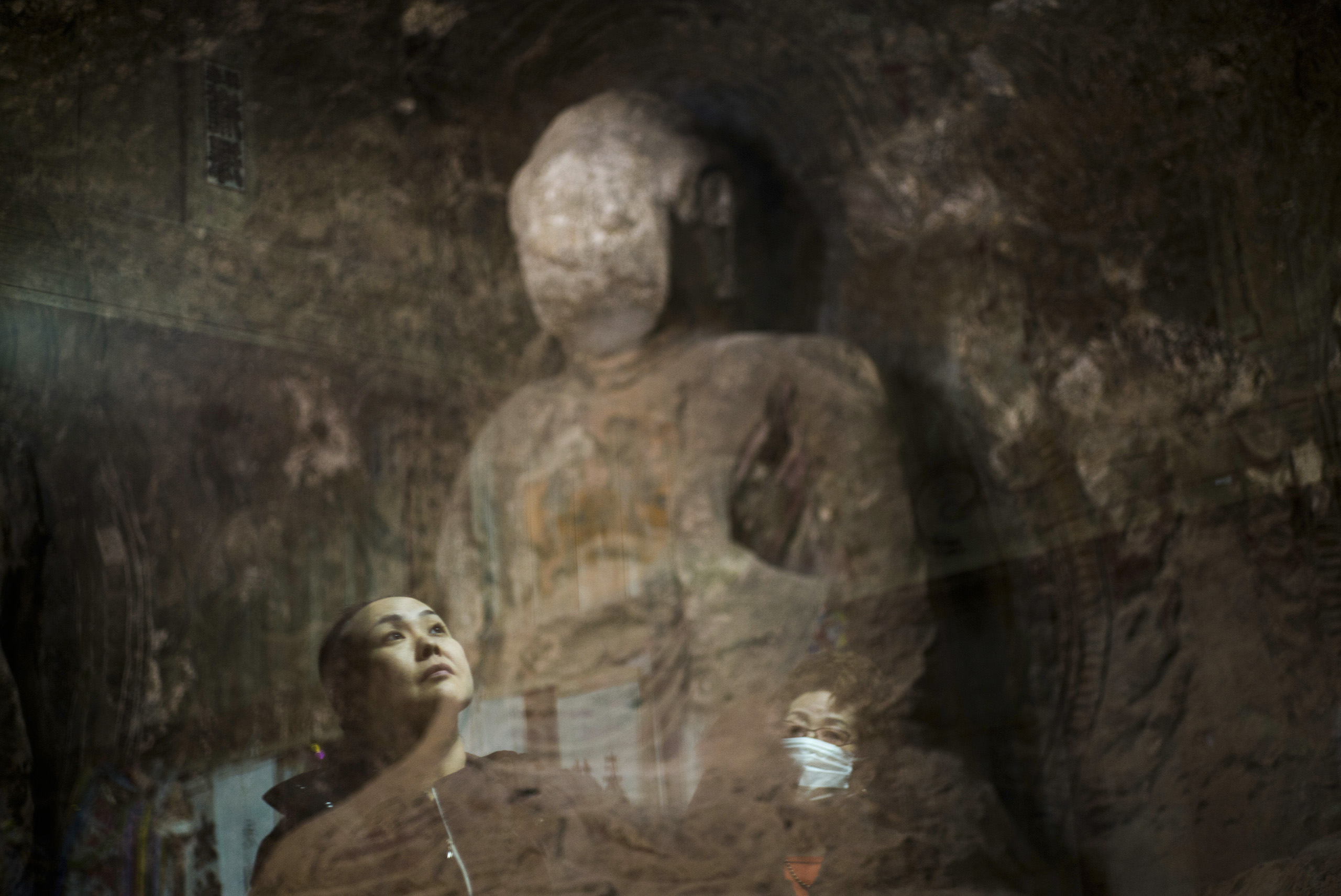 """Sachie Matsumoto, 43, and her mother look up at a Buddha statue called """"Daihisan no Sekibutsu,"""" or """"Stone Buddha statue of mountain of great sadness,"""" carved more than 1,000 years ago and situated inside the 20km exclusion zone, Osaka, Japan, March 6, 2016. Sachie would come here as a child."""
