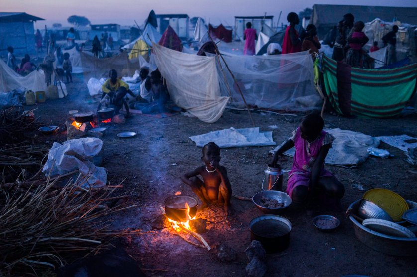 A mother prepares food for her child at a United Nations camp, where more than 100,00 displaced people seek security and food, in Bentiu, People walk past a drainage ditch in the United Nations camp in Bentiu, Unity State, South Sudan.