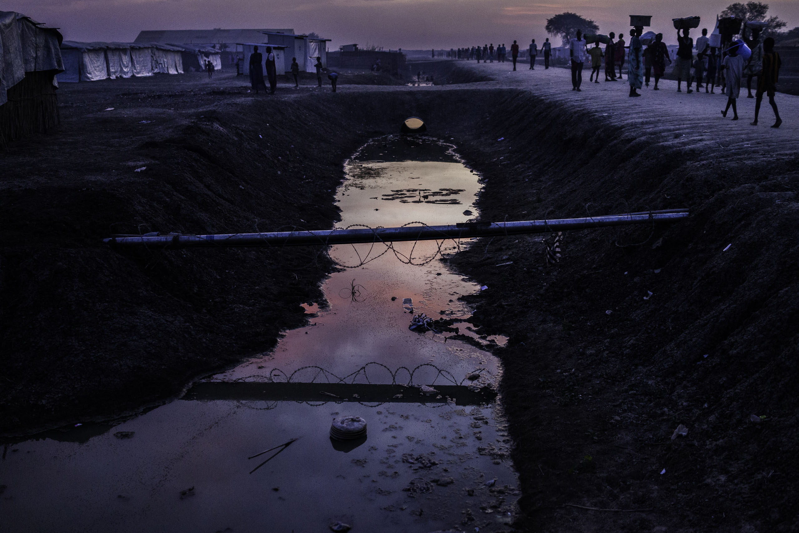 People walk past a drainage ditch in the United Nations camp in Bentiu, Unity State, South Sudan.