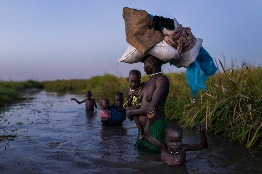 After receiving food at a distribution site, a woman and her five children walk through the cold swamps at dusk to her hiding place on Kok Island, Unity State, South Sudan.