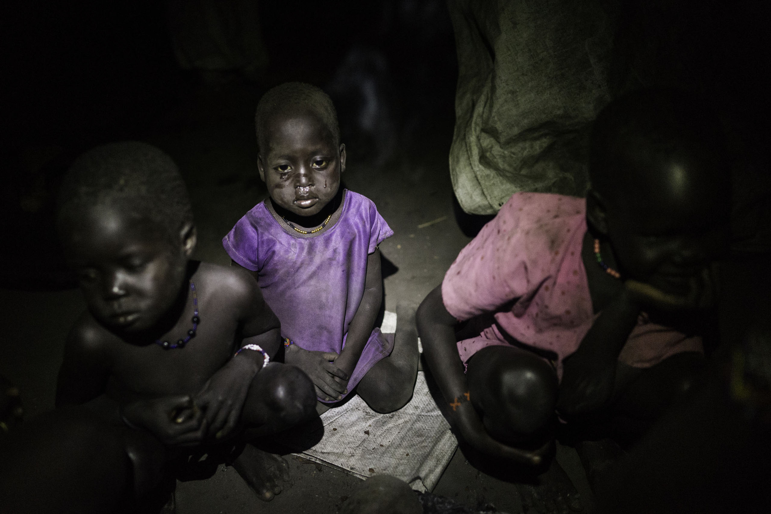 A child cries after walking through the cold swamps at night after collecting long awaited food distribution, Kok Island, Unity State, South Sudan.