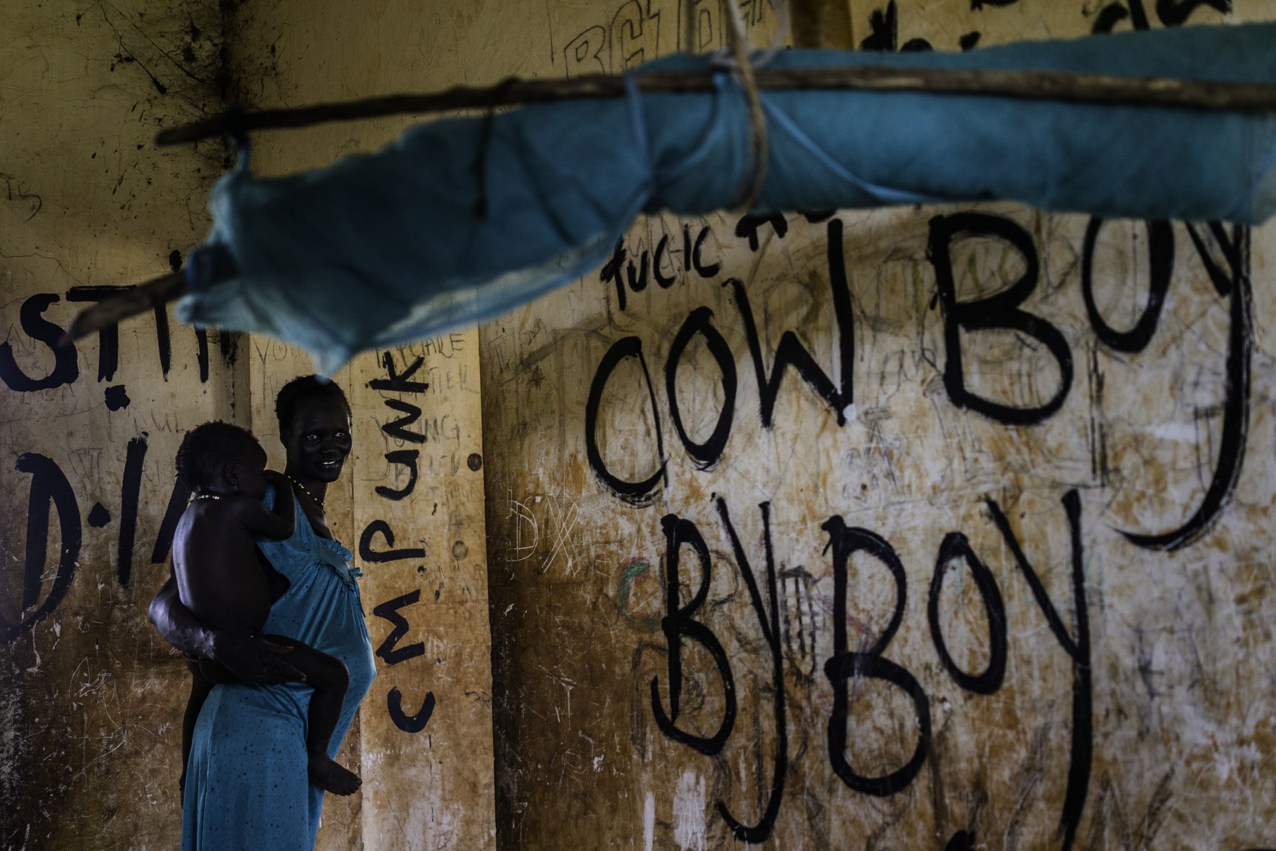 A mother holds her baby inside an abandoned building covered in graffiti, where over a dozen families have sought refuge from fighting, in Bentiu, Unity State, South Sudan.