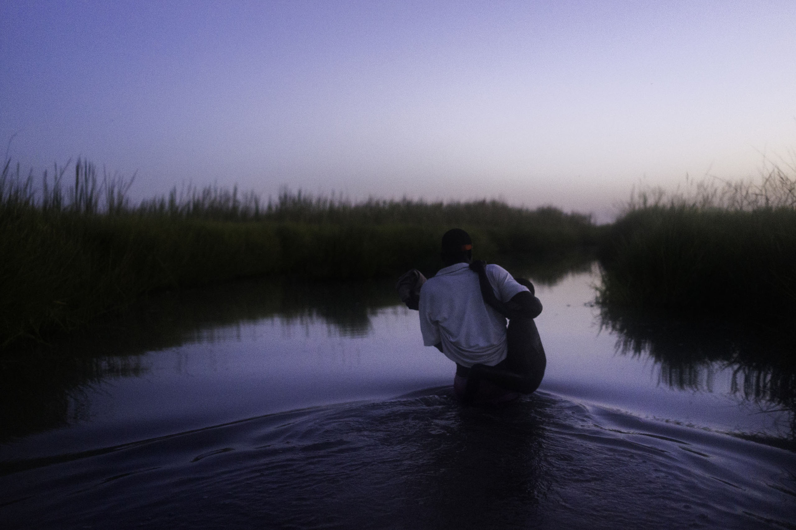 A staff worker with Doctors Without Borders helps a young boy cross a swamp at dusk to Kok Island, Unity State, South Sudan.