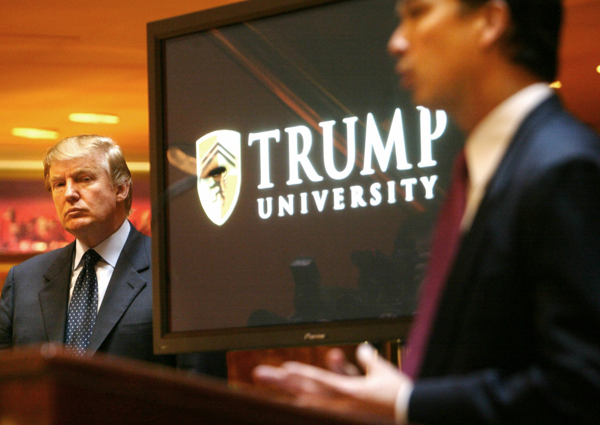 Donald Trump listens as Michael Sexton introduces him at a news conference in New York where he announced the establishment of Trump University on May 23, 2005.