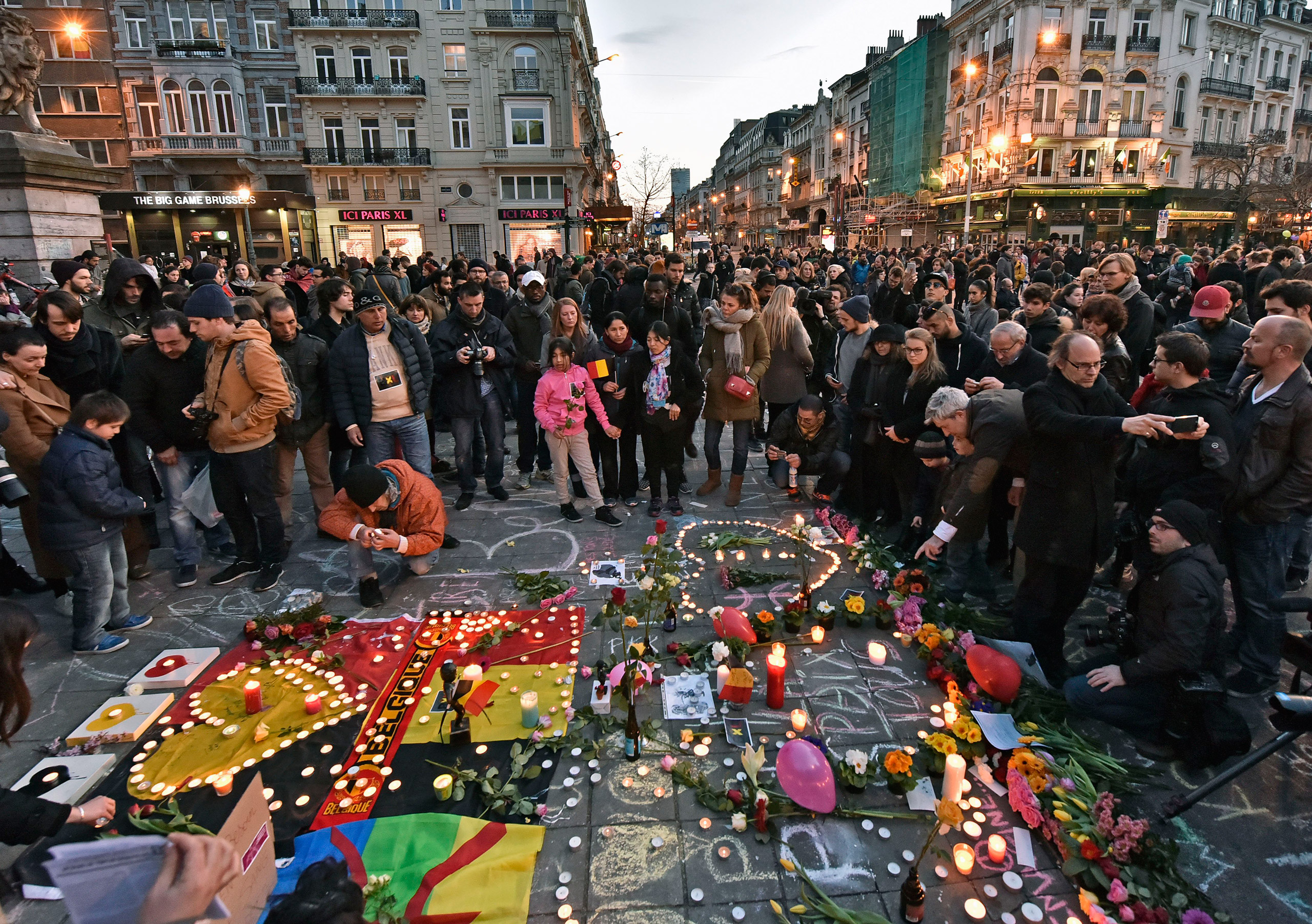 People bring flowers and candles to mourn at the Place de la Bourse in the center of Brussels, Belgium, March 22, 2016.