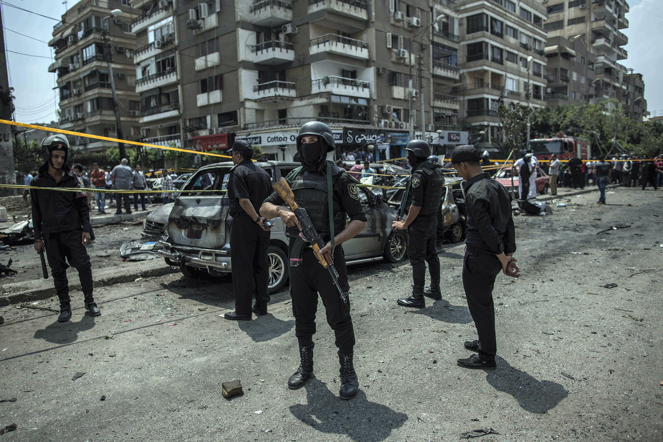 In this June 29, 2015, file photo, Egyptian policemen stand guard at the site of a bombing that killed Egypt's top prosecutor, Hisham Barakat, who oversaw cases against thousands of Islamists, in Cairo, Egypt.