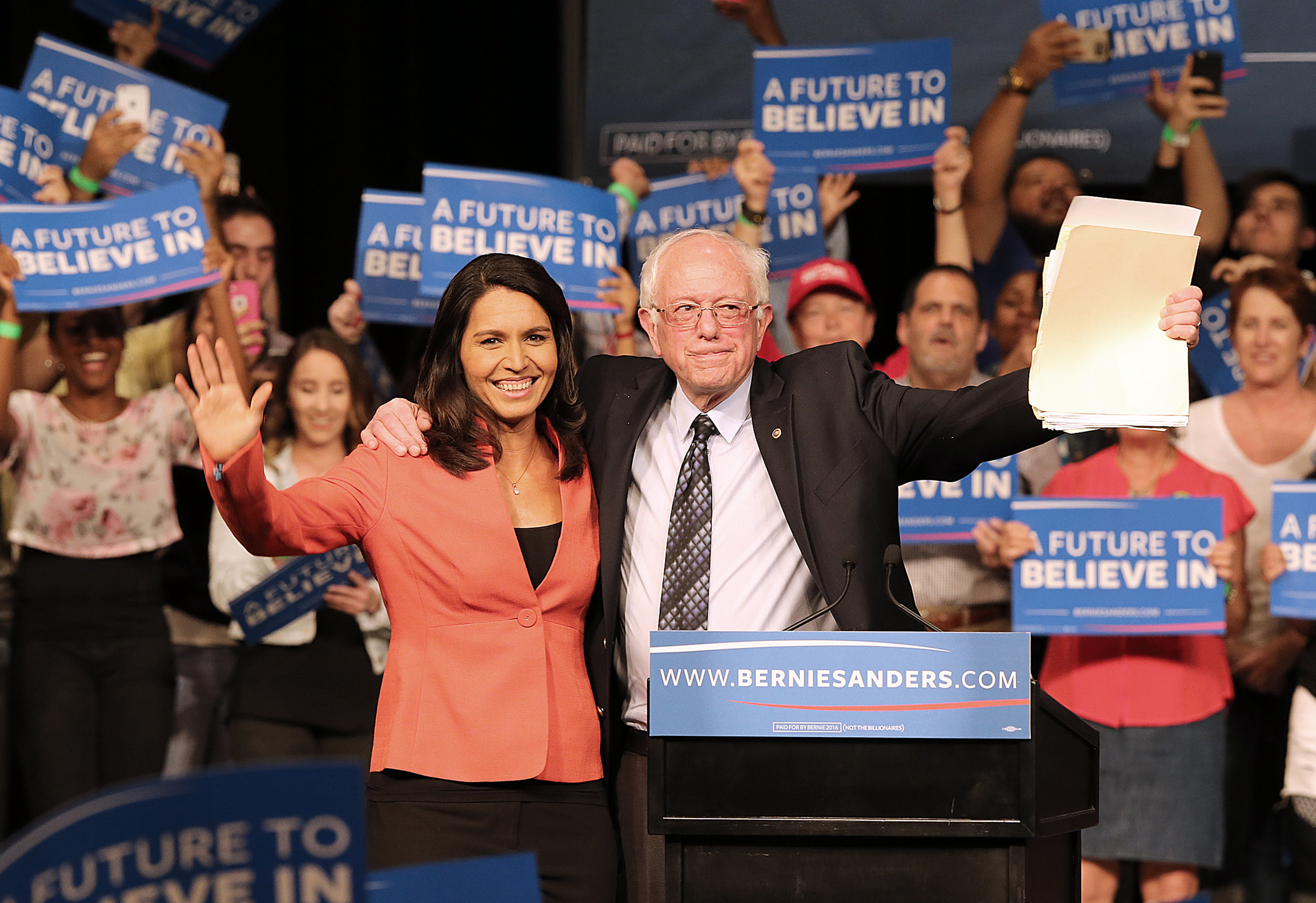 Rep. Tulsi Gabbard, D-Hawaii, and Democratic presidential candidate Sen. Bernie Sanders wave to supporters during a campaign event in Miami on Tuesday, March 8, 2016.