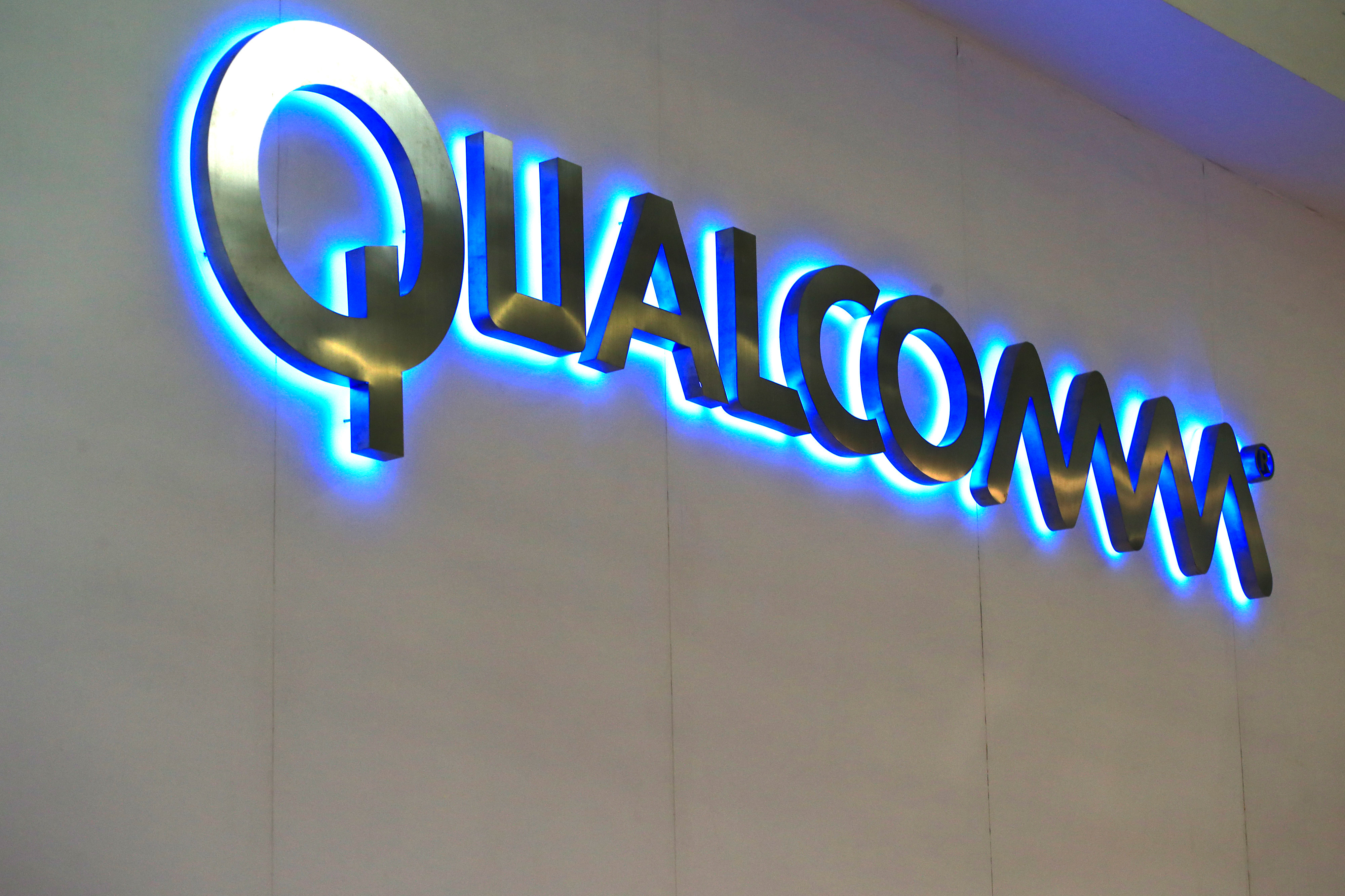 A logo sits illuminated outside the Qualcomm Inc. pavilion at the Mobile World Congress in Barcelona, Spain, March 2, 2015