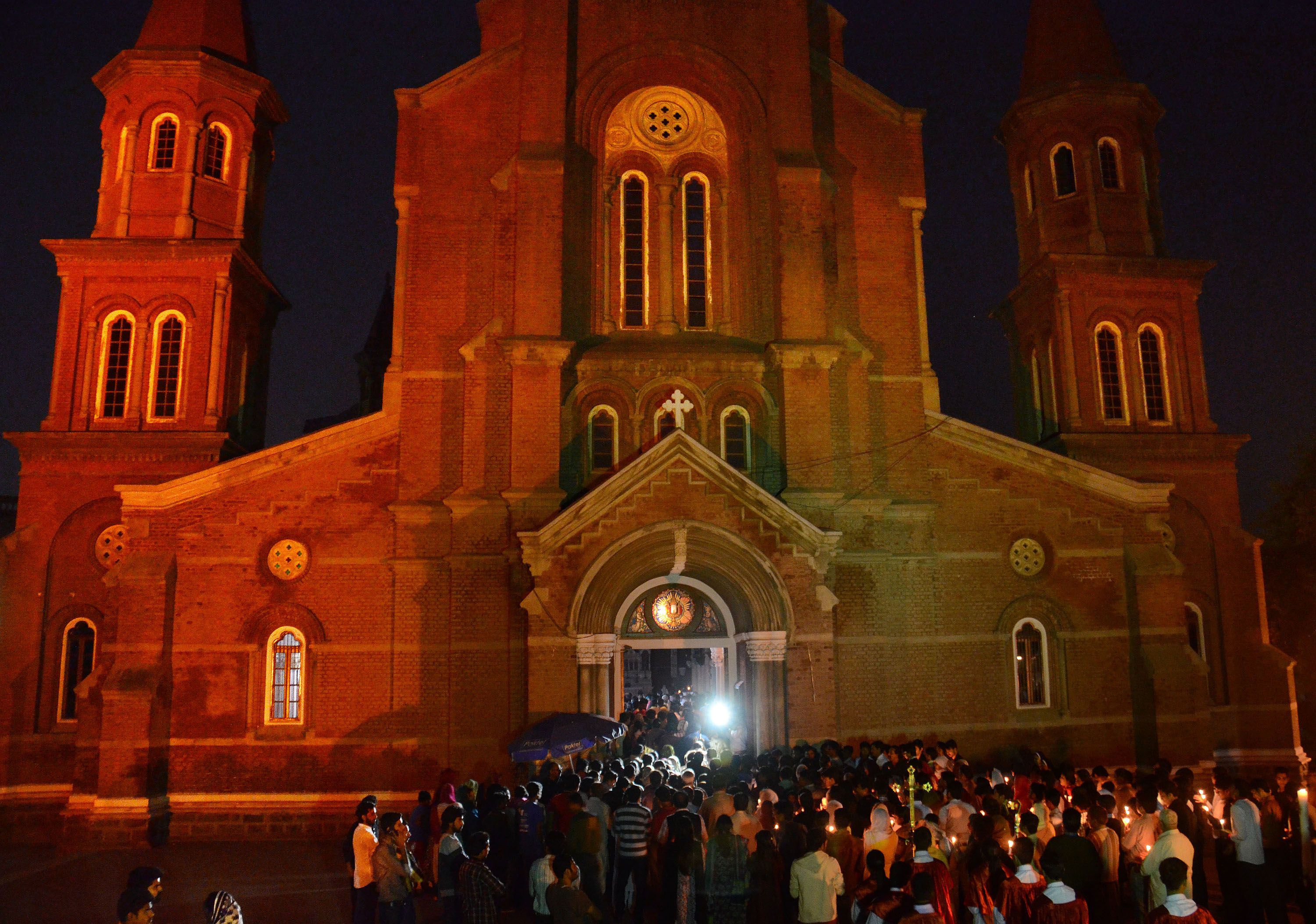 Pakistani Christian worshipers pray and hold candles during an Easter vigil mass at Regal Church, Lahore on April 5, 2015.