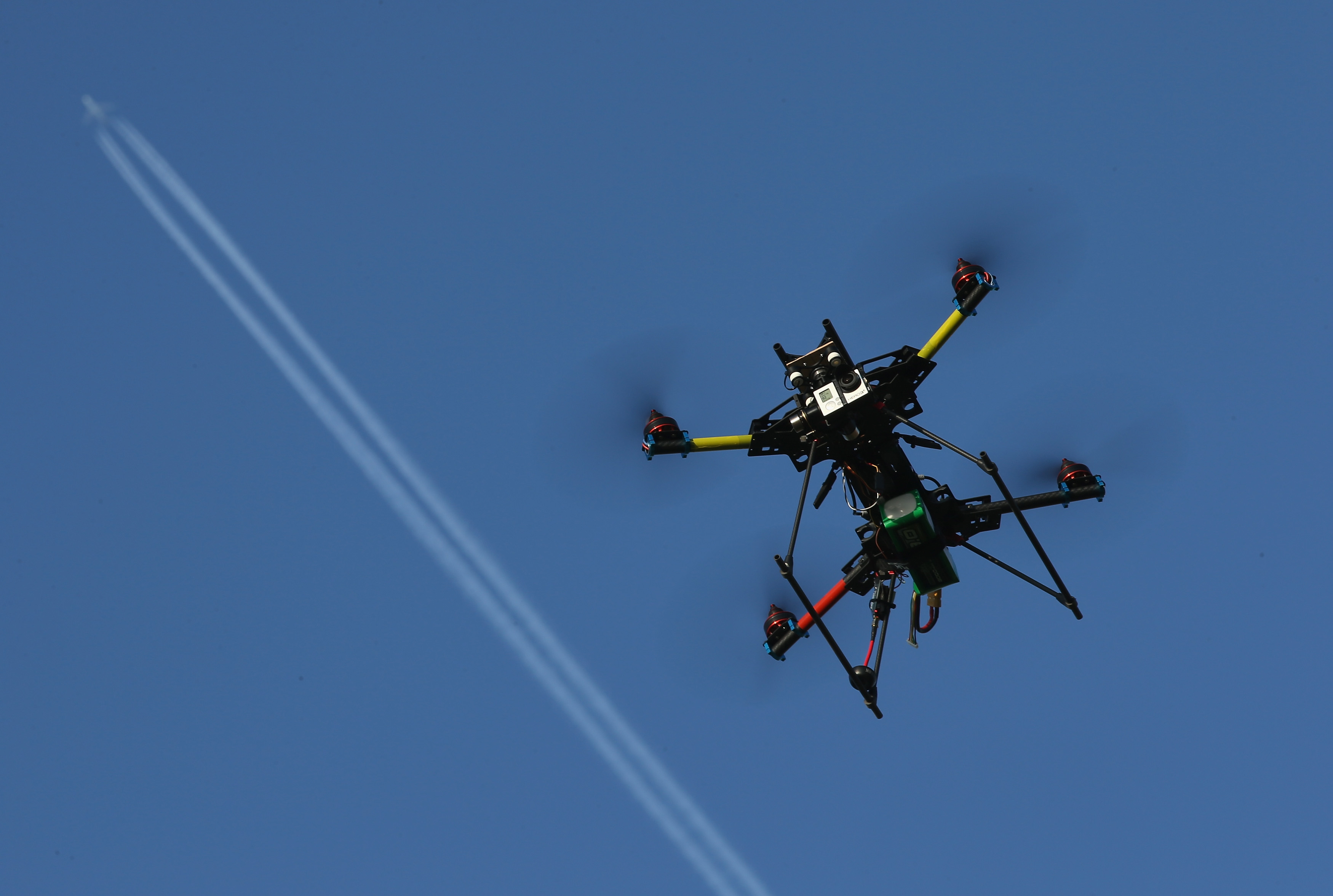 A commercial passenger plane flies overhead as a multirotor quadcopter drone used for aerial photography flies on June 7, 2011 near Zeestow, Germany.  (Sean Gallup--Getty Images)