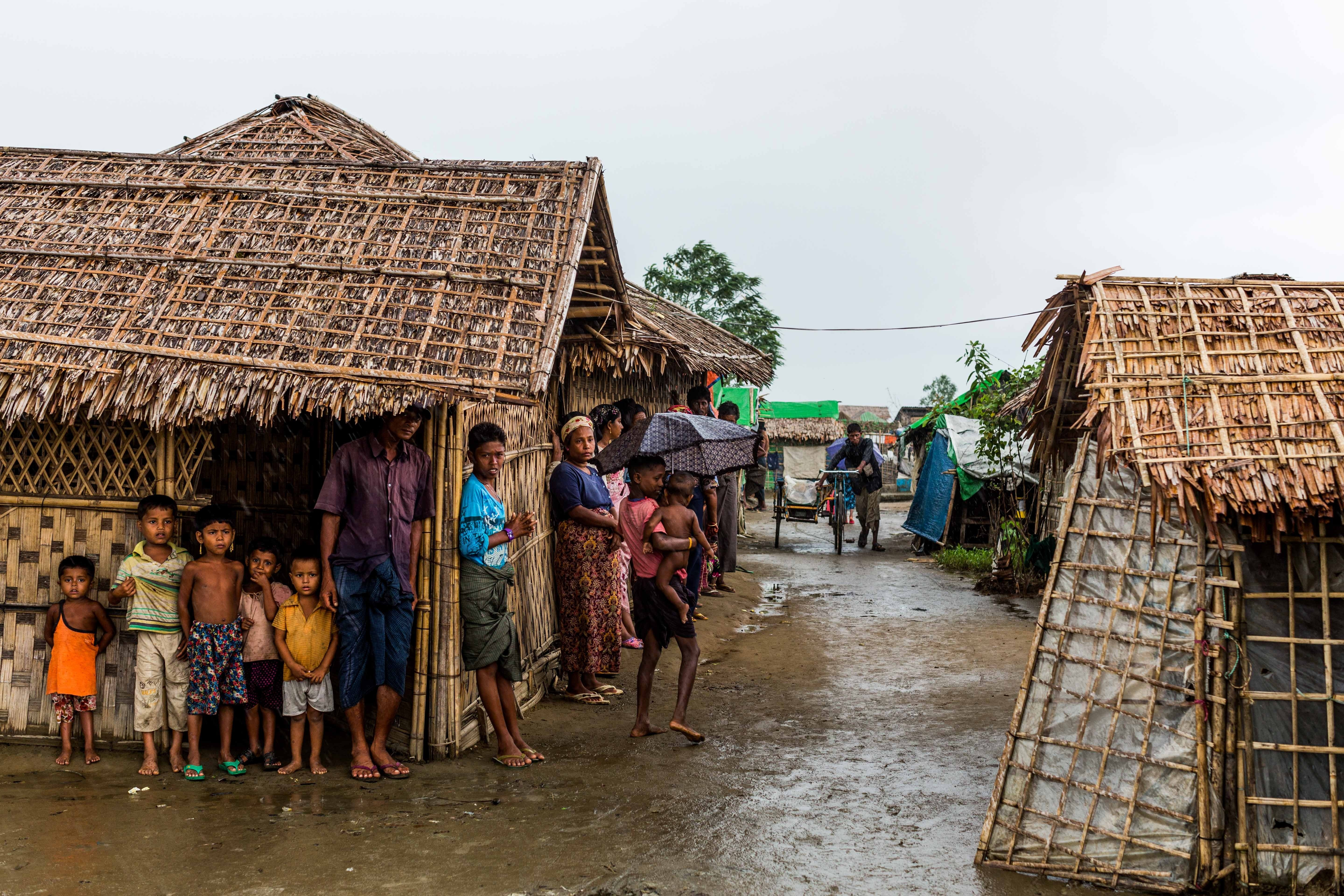Rohingya refugees seek shelter from the monsoon rains inside a camp for internally displaced persons outside Sittwe, in Burma's Rakhine state, on July 17, 2015