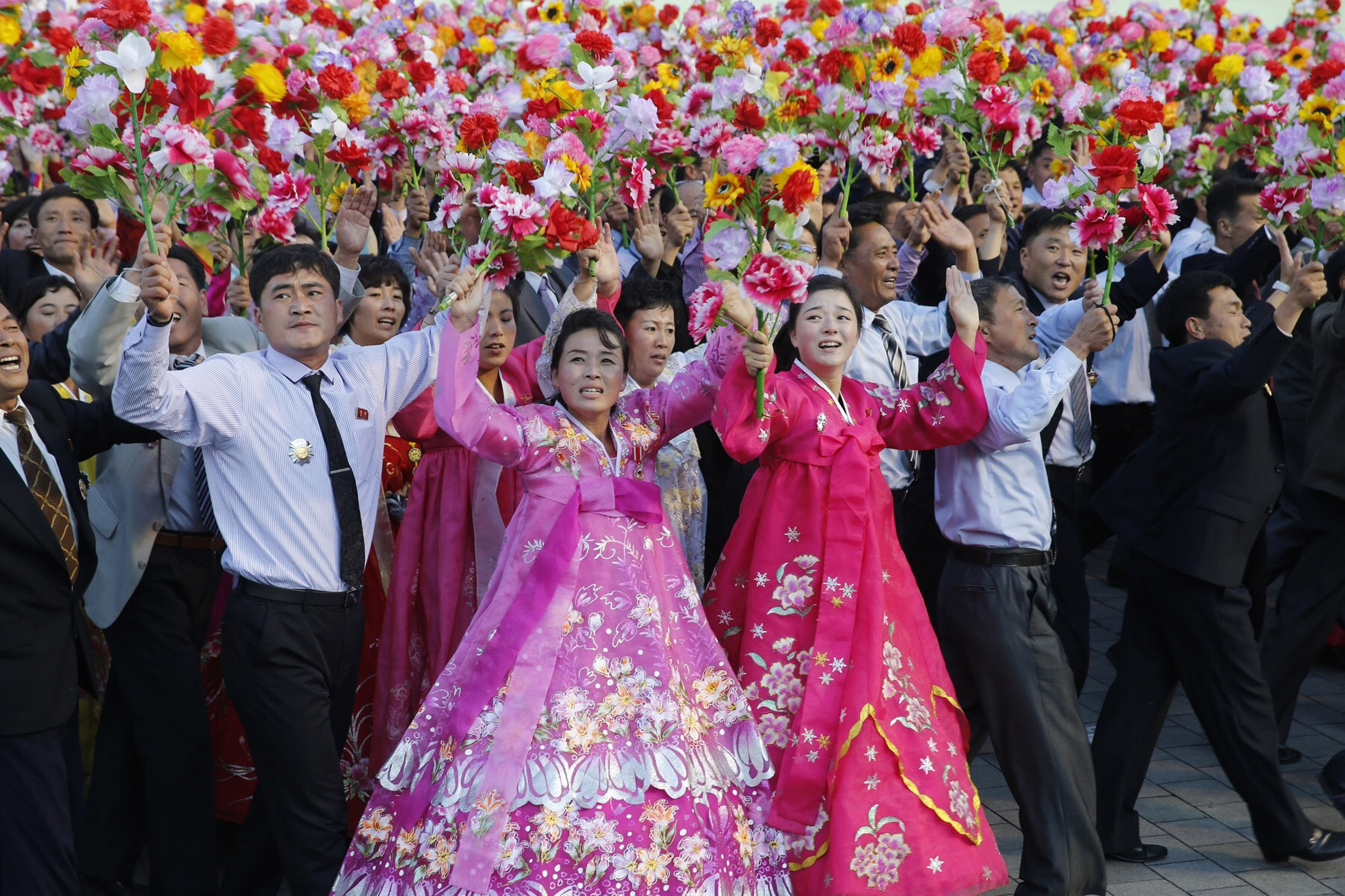 Participants wave flowers during a mass military parade at Kim Il Sung Square to mark the 70th anniversary of its ruling Workers' Party of Korea on Oct. 10. 2015, in Pyongyang