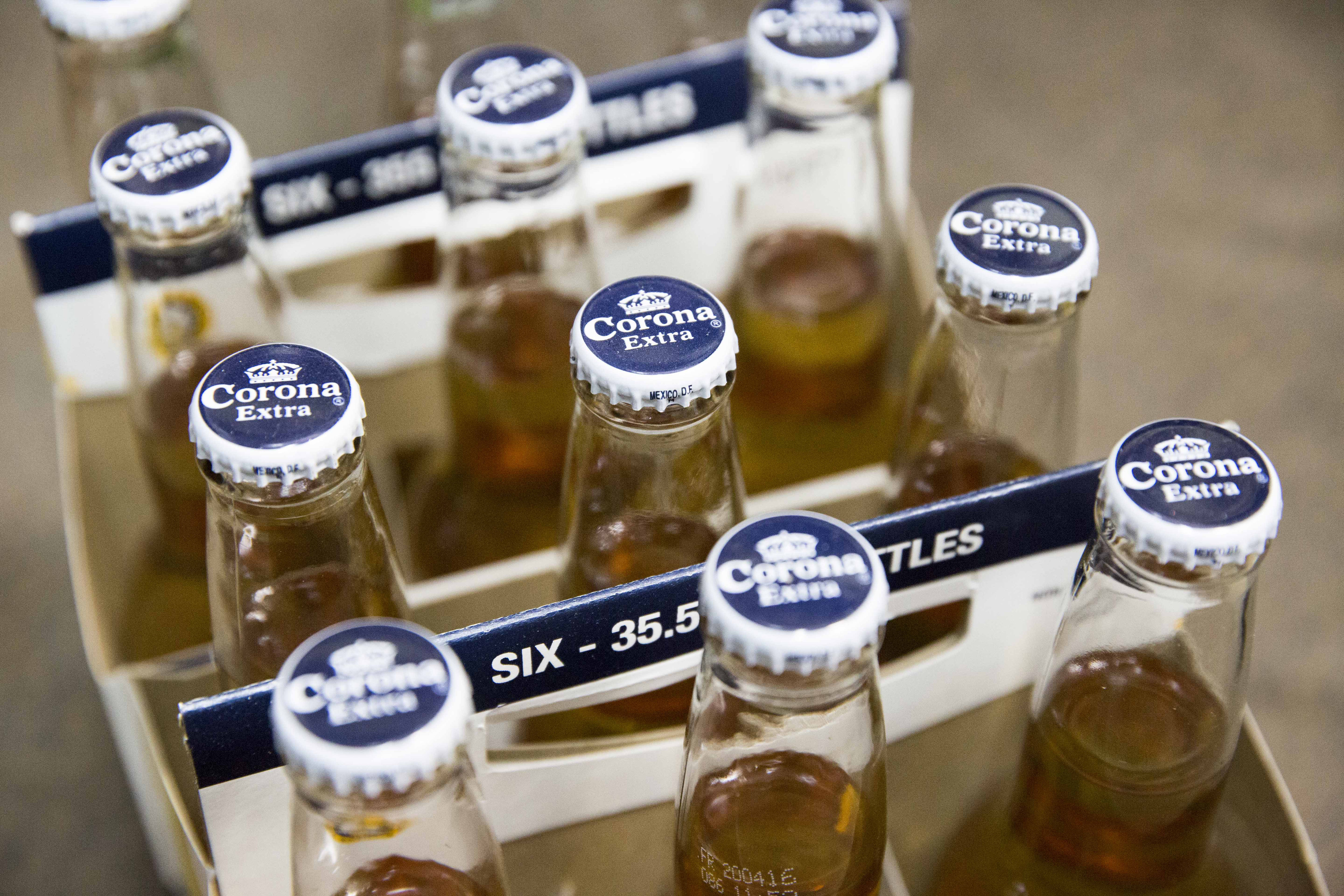 Six packs of bottled Corona beer, produced by Anheuser-Busch InBev NV, sit on display in a store in Paris, France, on Thursday, Oct. 15, 2015. AB Inbev is planning to sell bonds worth as much as $55 billion to finance its $106 billion takeover of SABMiller Plc, setting a record for debt issuance to fund a corporate acquisition, according to people familiar with the matter.