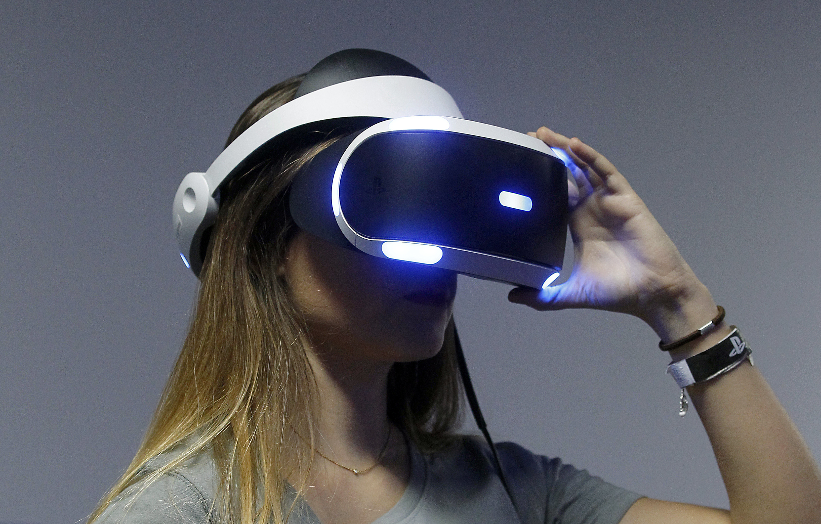 A gamer plays a video game with the virtual reality head-mounted display 'Playstation VR' during the 'Paris Games week' at Parc des Expositions Porte de Versailles on October 28, 2015 in Paris, France.