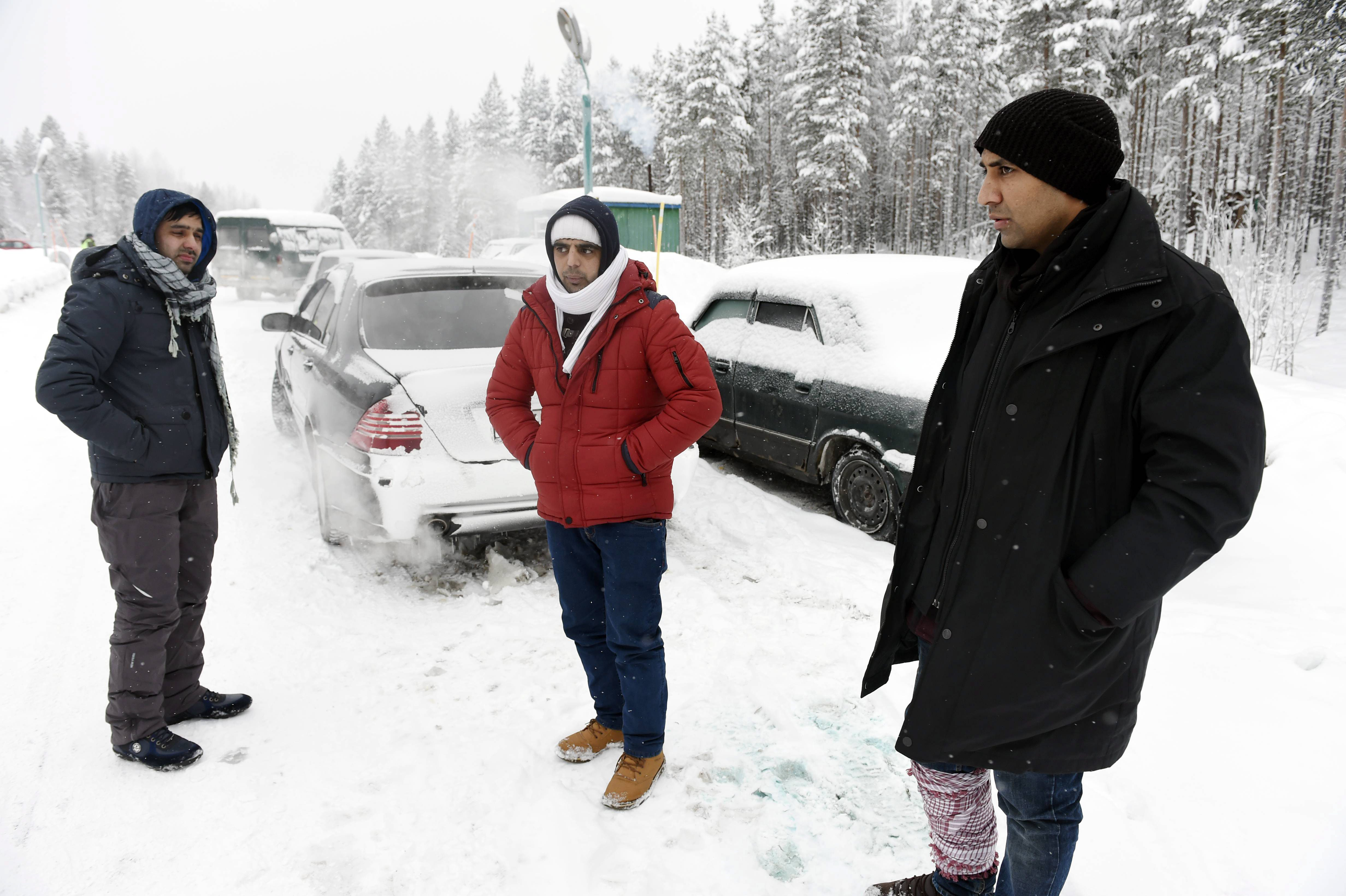 Asylum seekers Rahmatullah, left, and Nazirulhag, center, from Afghanistan and Fida Hussain from Pakistan wait on the Russian side of the border on Jan. 23, 2016