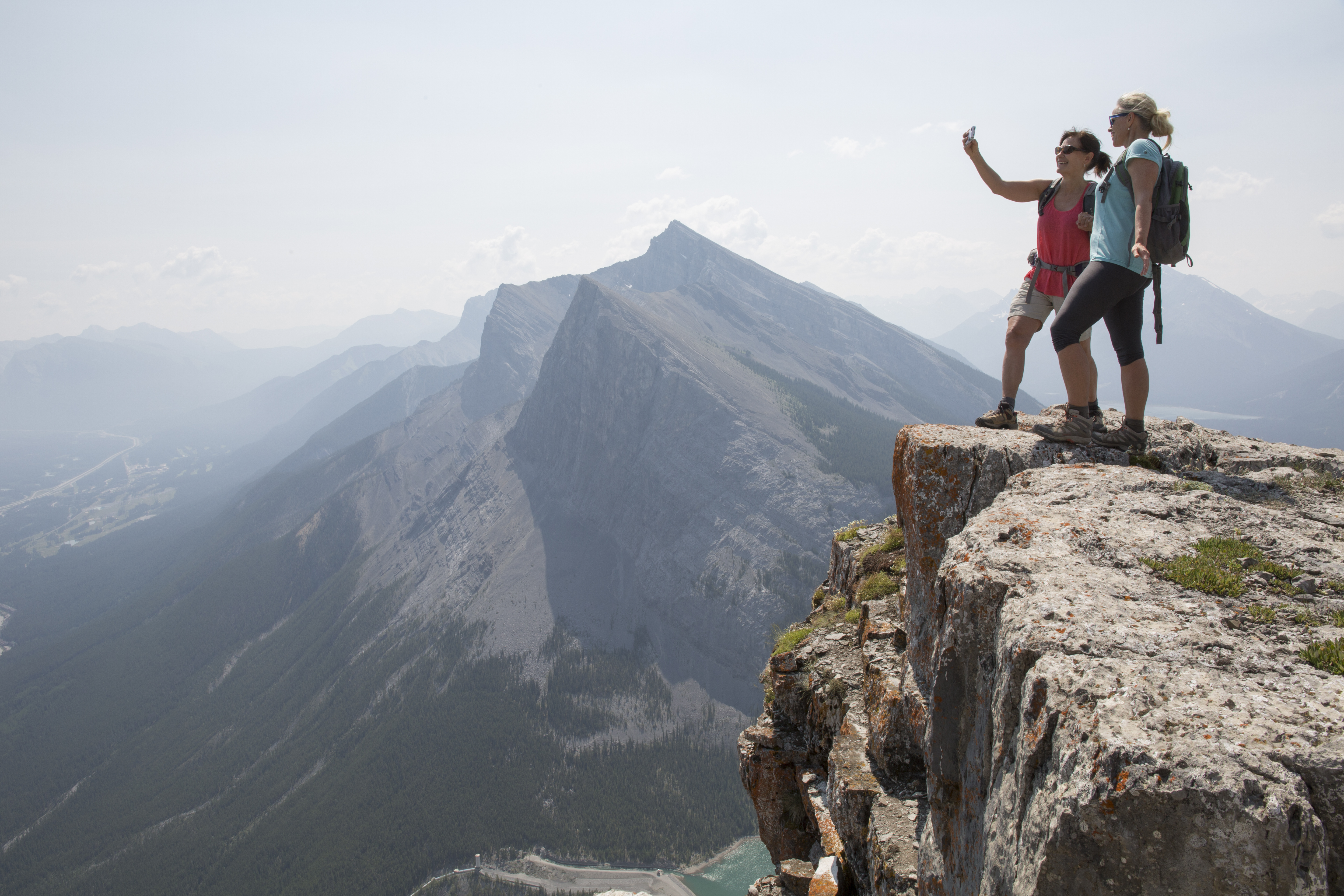 Female hikers take selfie pic on top of mountain